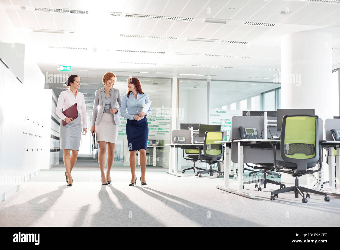 Full-length of businesswomen with file folders walking in office - Stock Image
