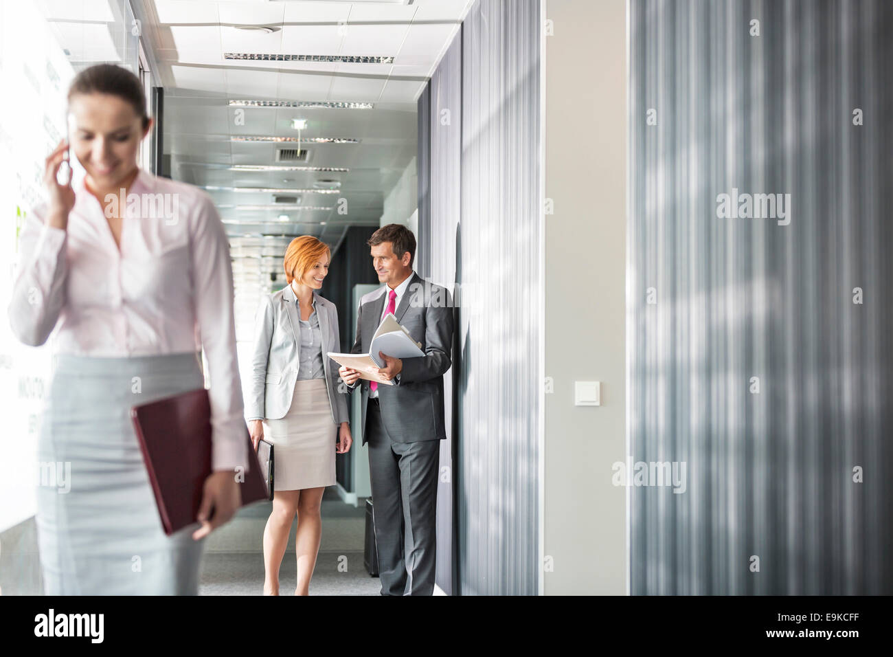 Business people discussing in corridor with colleague using cell phone in foreground - Stock Image