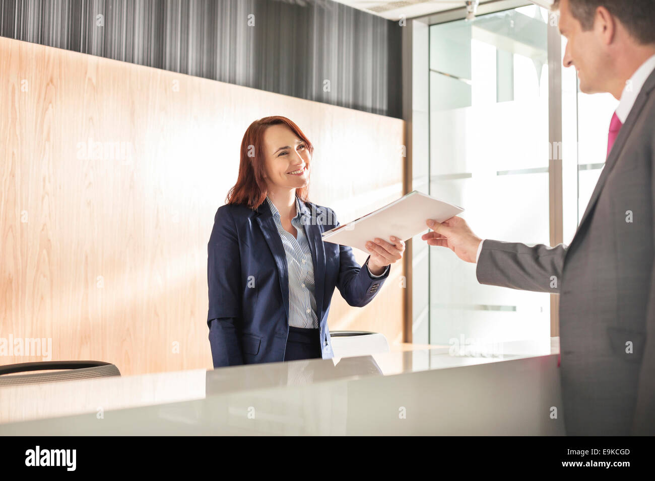 Businessman receiving document from receptionist in office - Stock Image