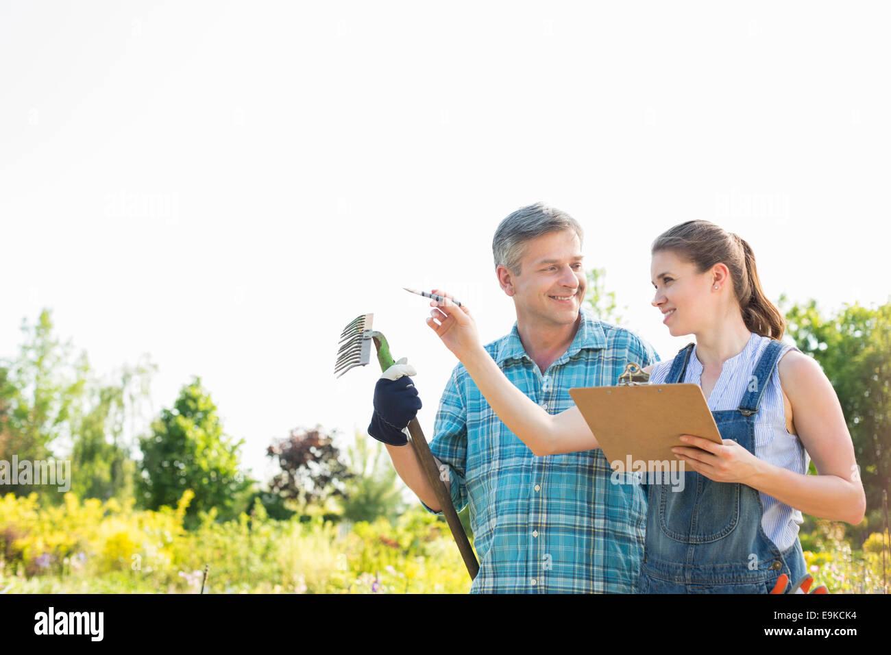Happy female supervisor explaining something to gardener at plant nursery - Stock Image