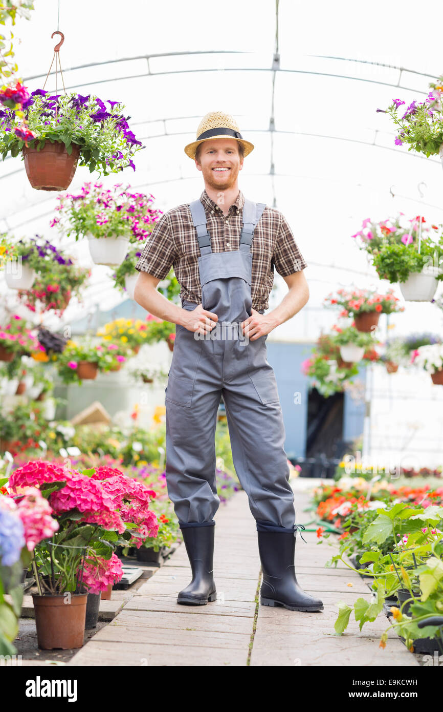 Full-length portrait of happy gardener standing at greenhouse - Stock Image
