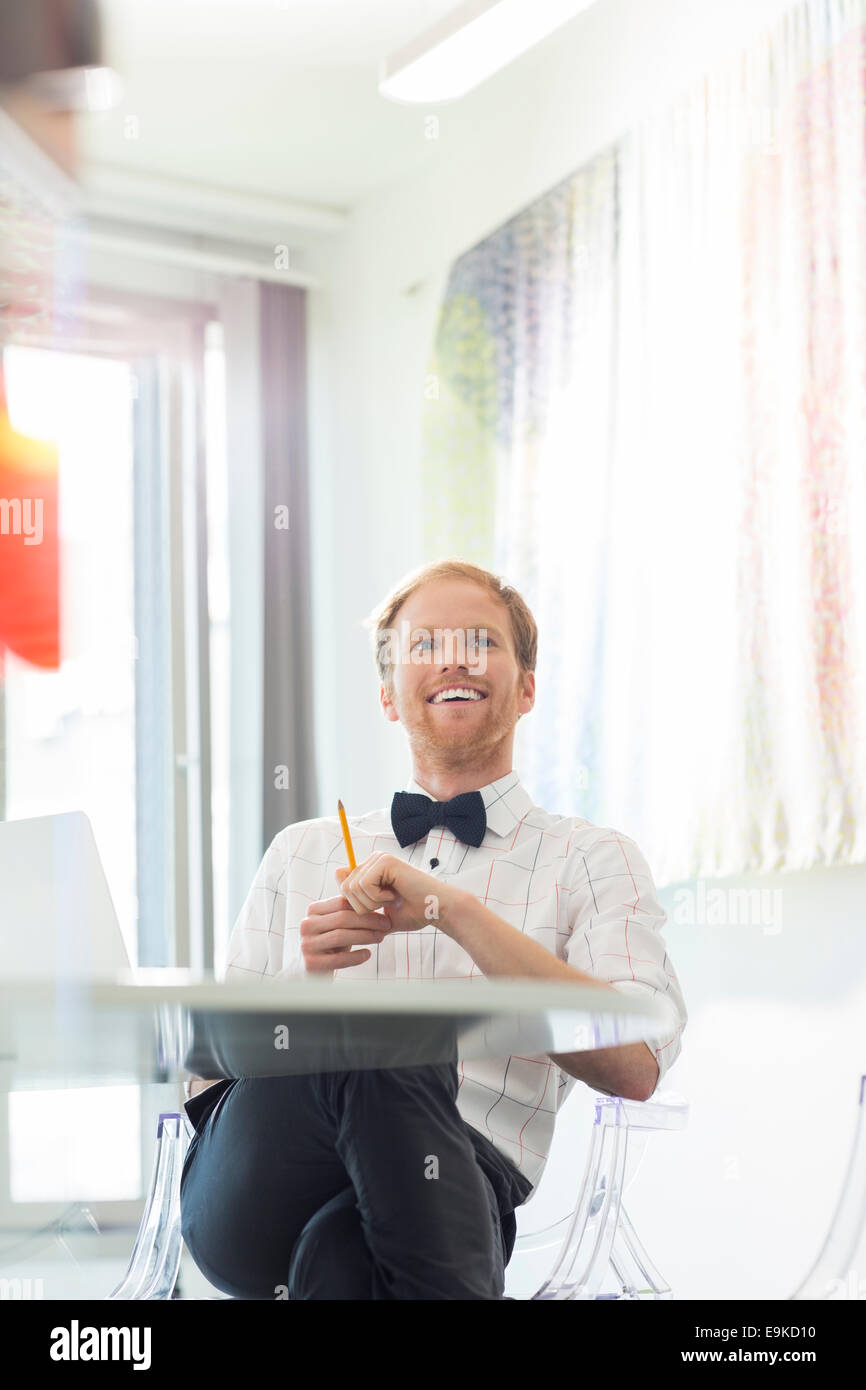 Happy businessman looking away in creative office - Stock Image