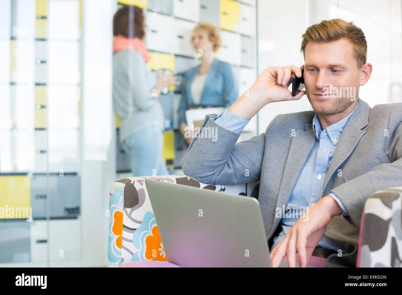 Businessman using technologies with colleagues discussing in background at creative office - Stock Image
