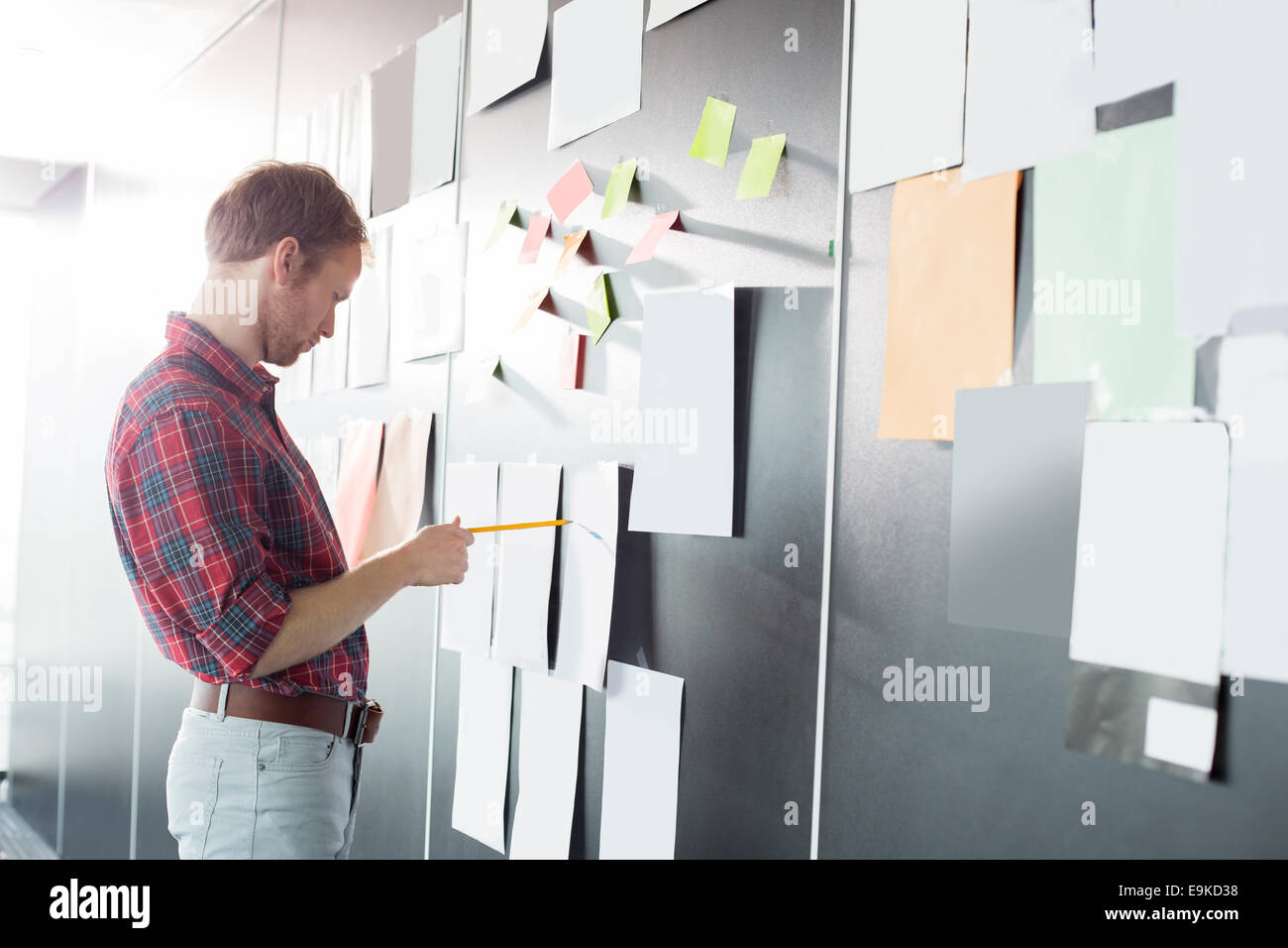 Businessman analyzing documents on wall at creative office - Stock Image