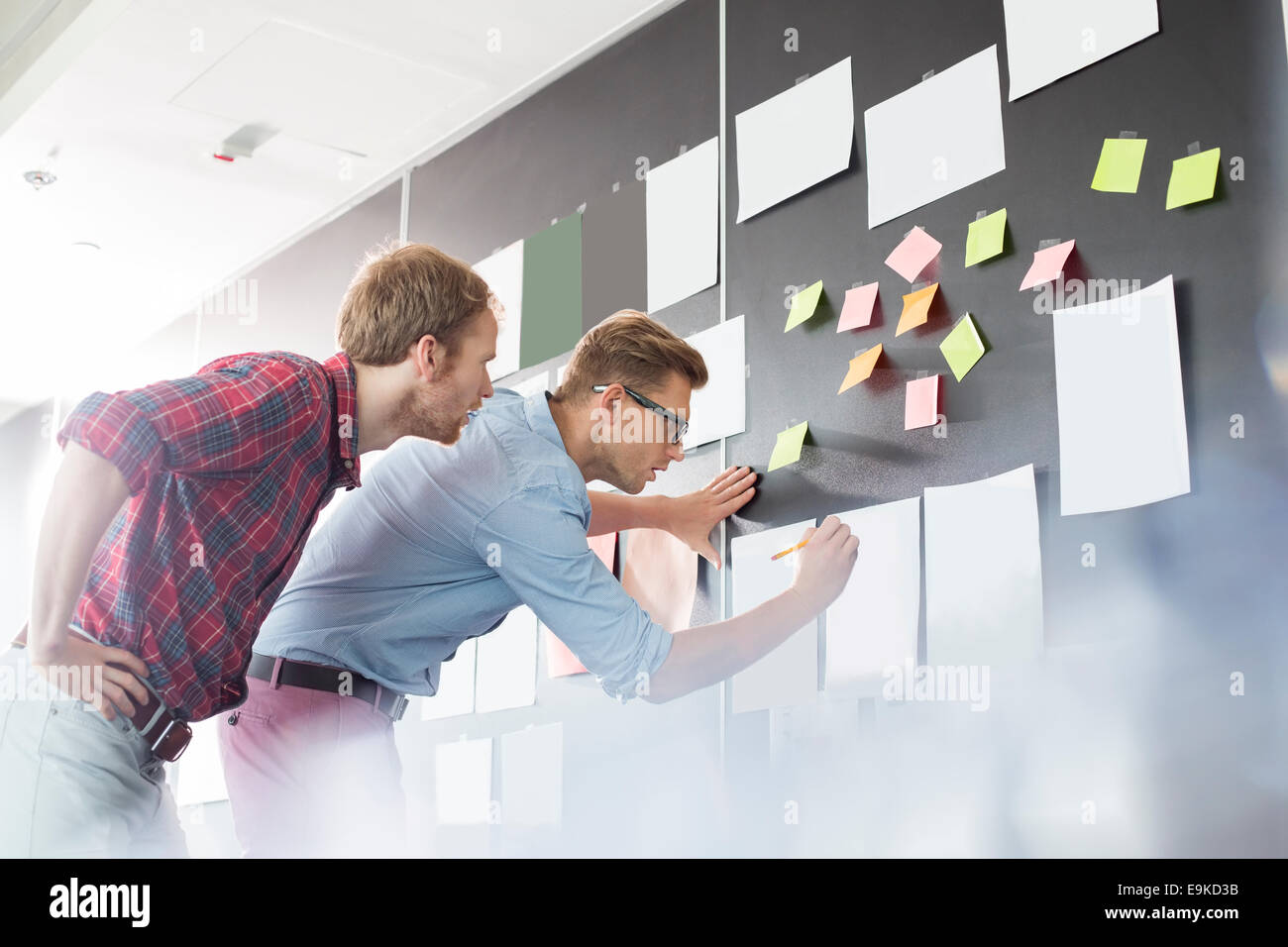 Businessmen analyzing documents on wall in office - Stock Image