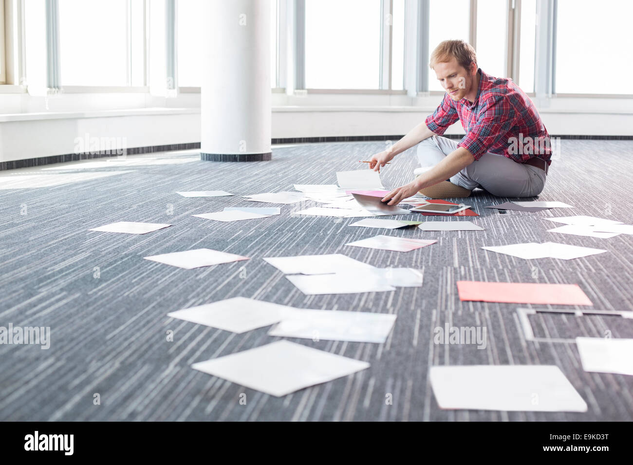 Businessman analyzing photographs while sitting on floor at creative office - Stock Image