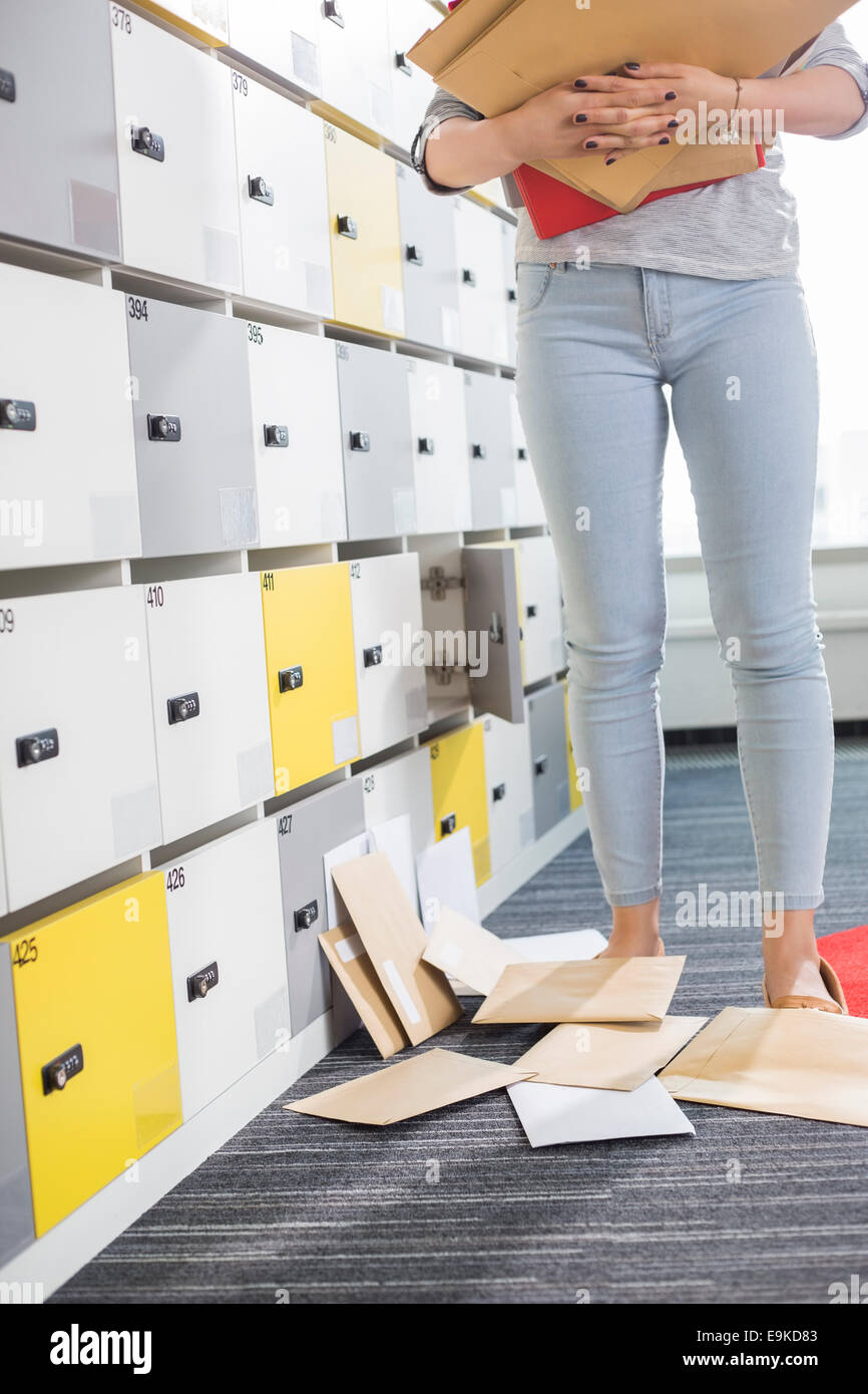 Low section of businesswoman standing by fallen documents in locker room at creative office - Stock Image