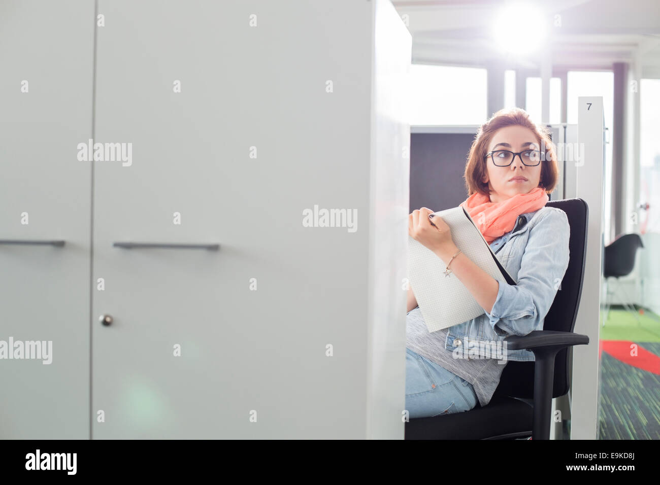 Businesswoman holding notepad while sitting on chair at creative office - Stock Image