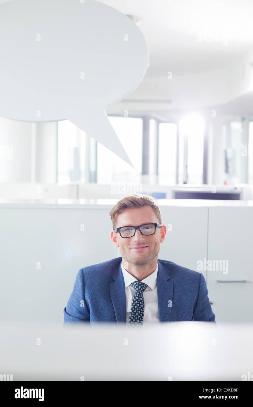 Portrait of confident businessman with speech bubble in office - Stock Image