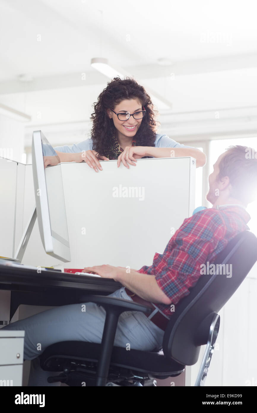 Business people talking over cubicle wall - Stock Image