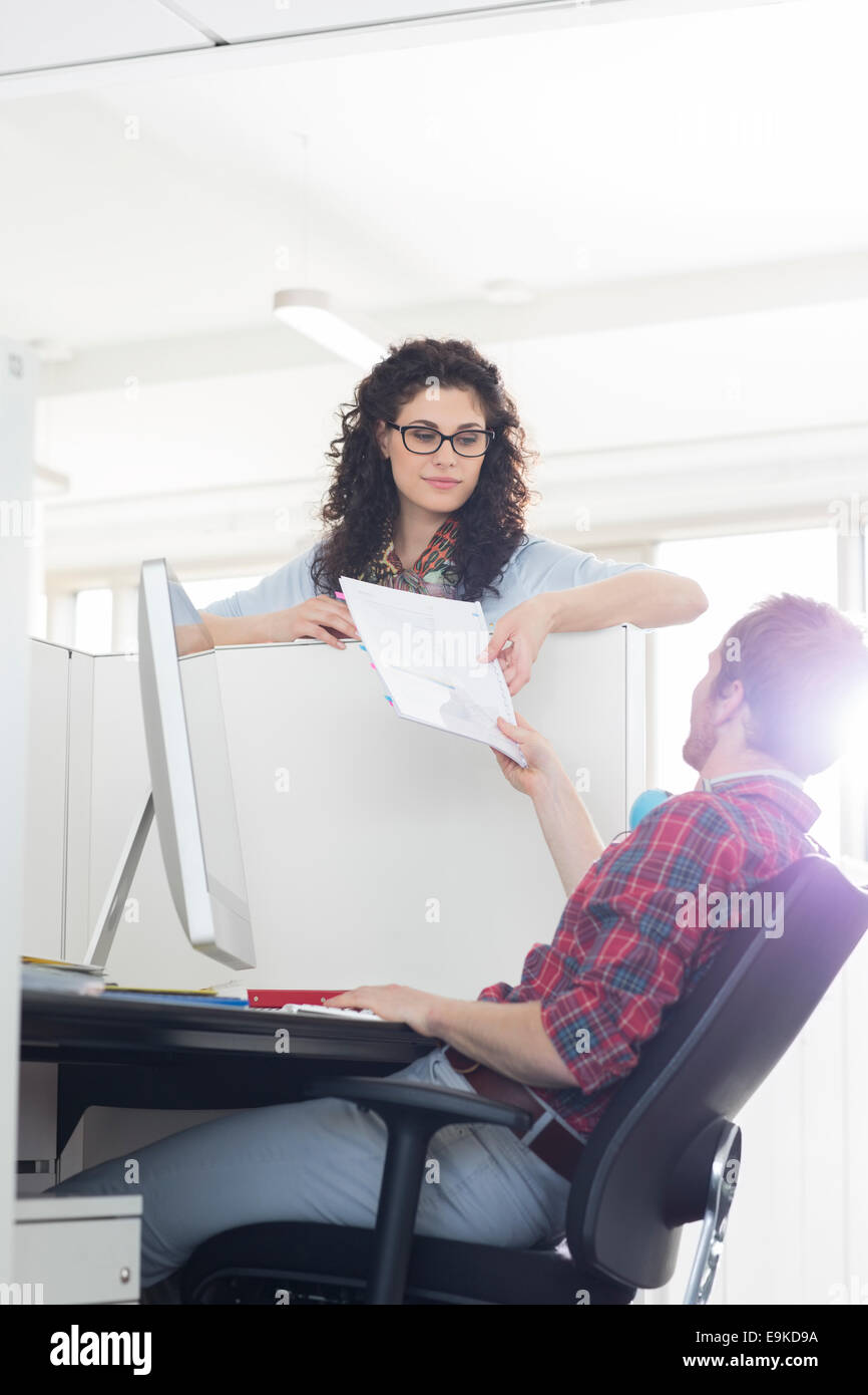 Businessman handing over document to female colleague over cubicle wall - Stock Image