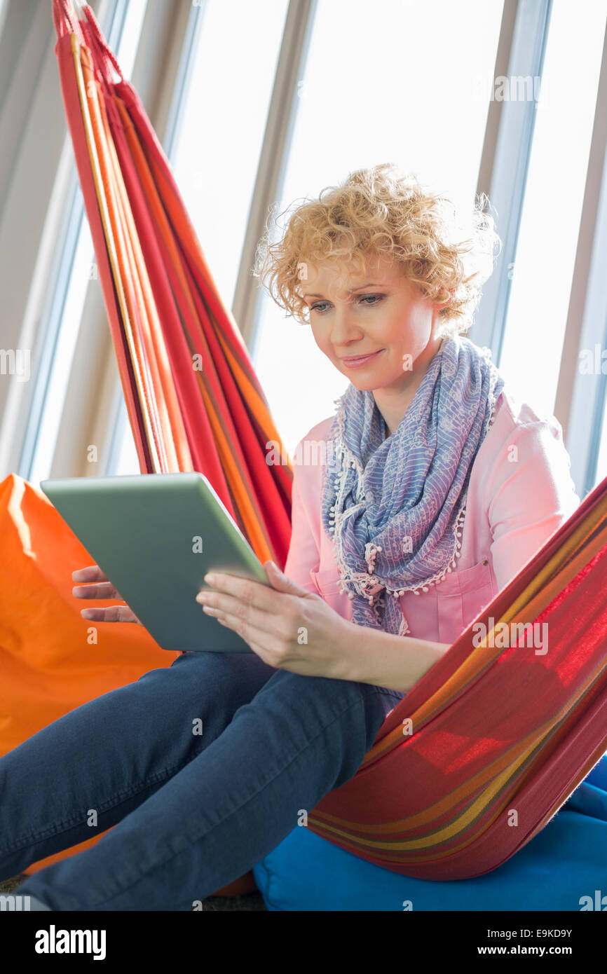 Creative businesswoman using digital tablet on hammock in office - Stock Image