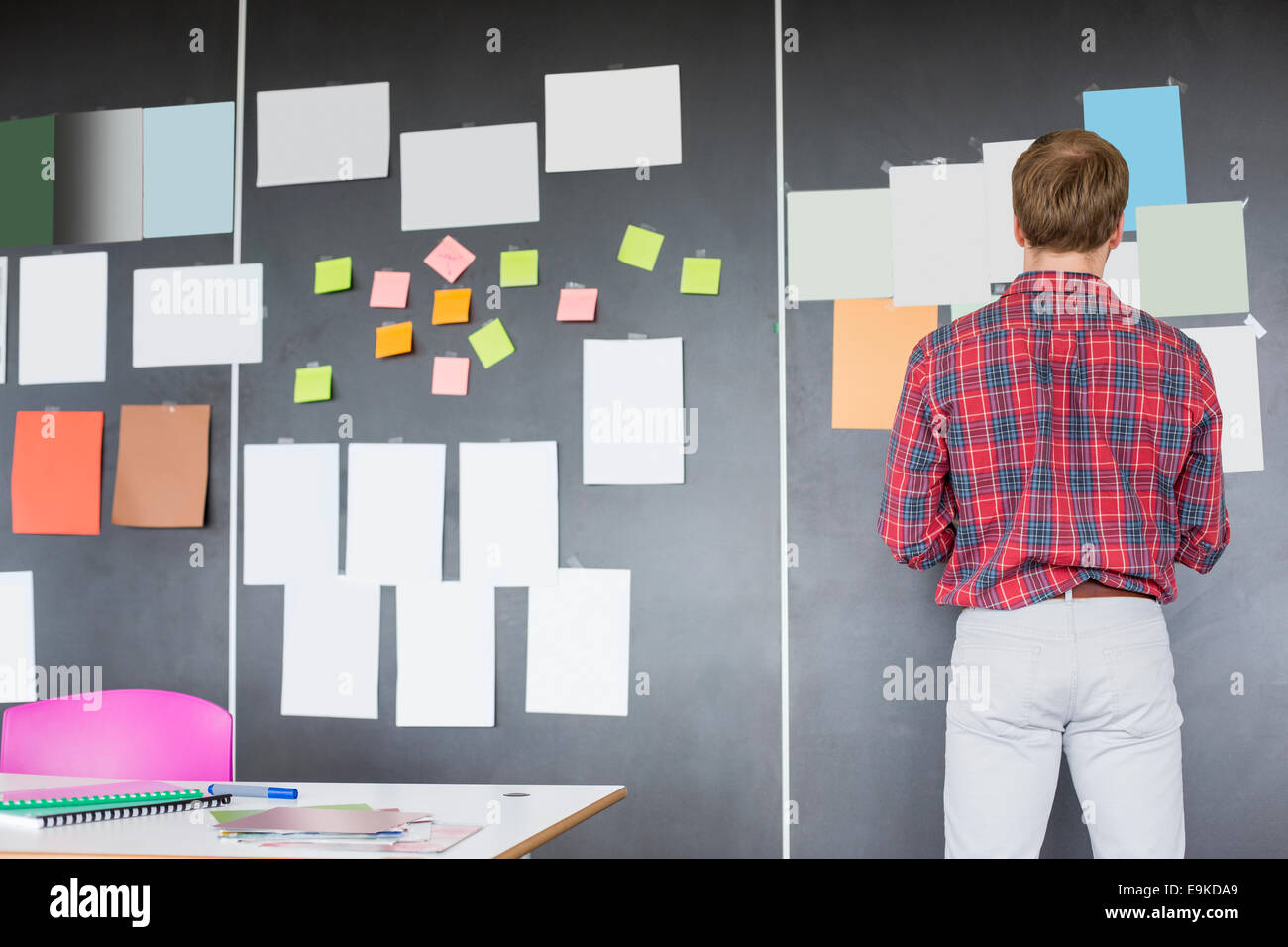 Rear view of businessman analyzing documents on wall at creative office - Stock Image