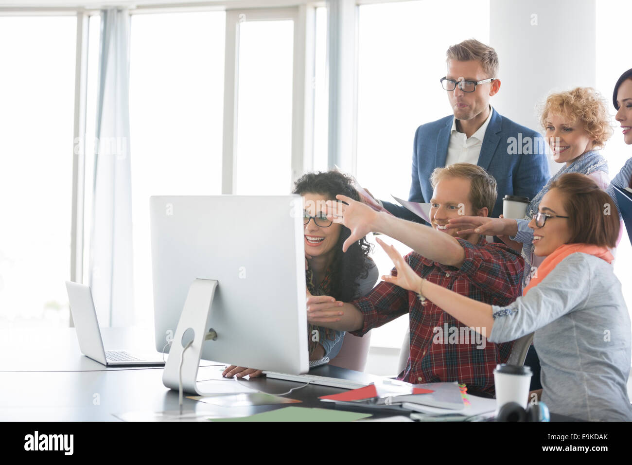 Business people using computer in office - Stock Image