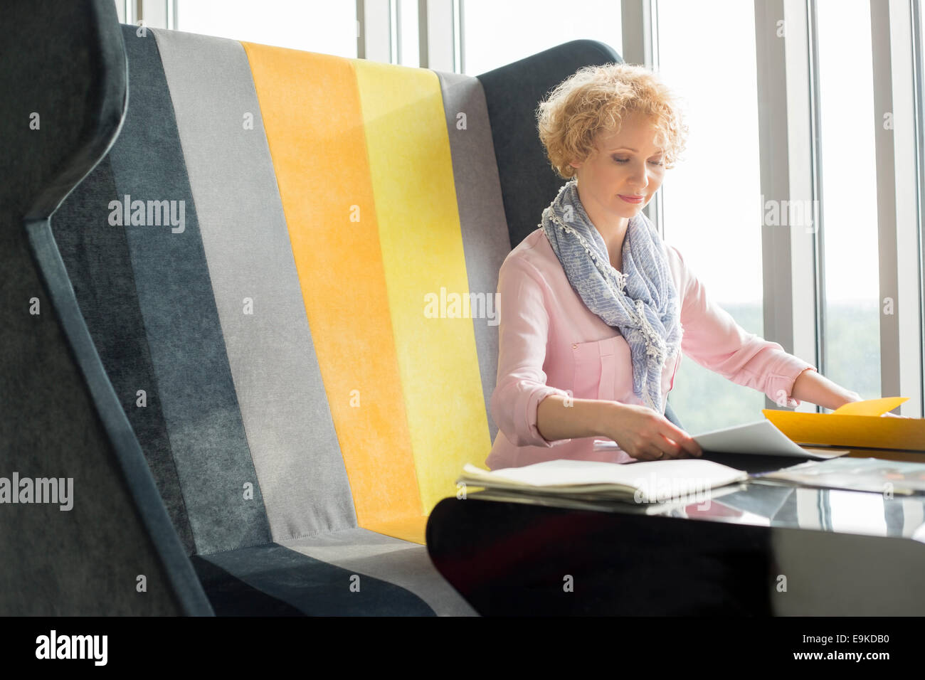 Mid adult businesswoman reading documents at desk in office - Stock Image