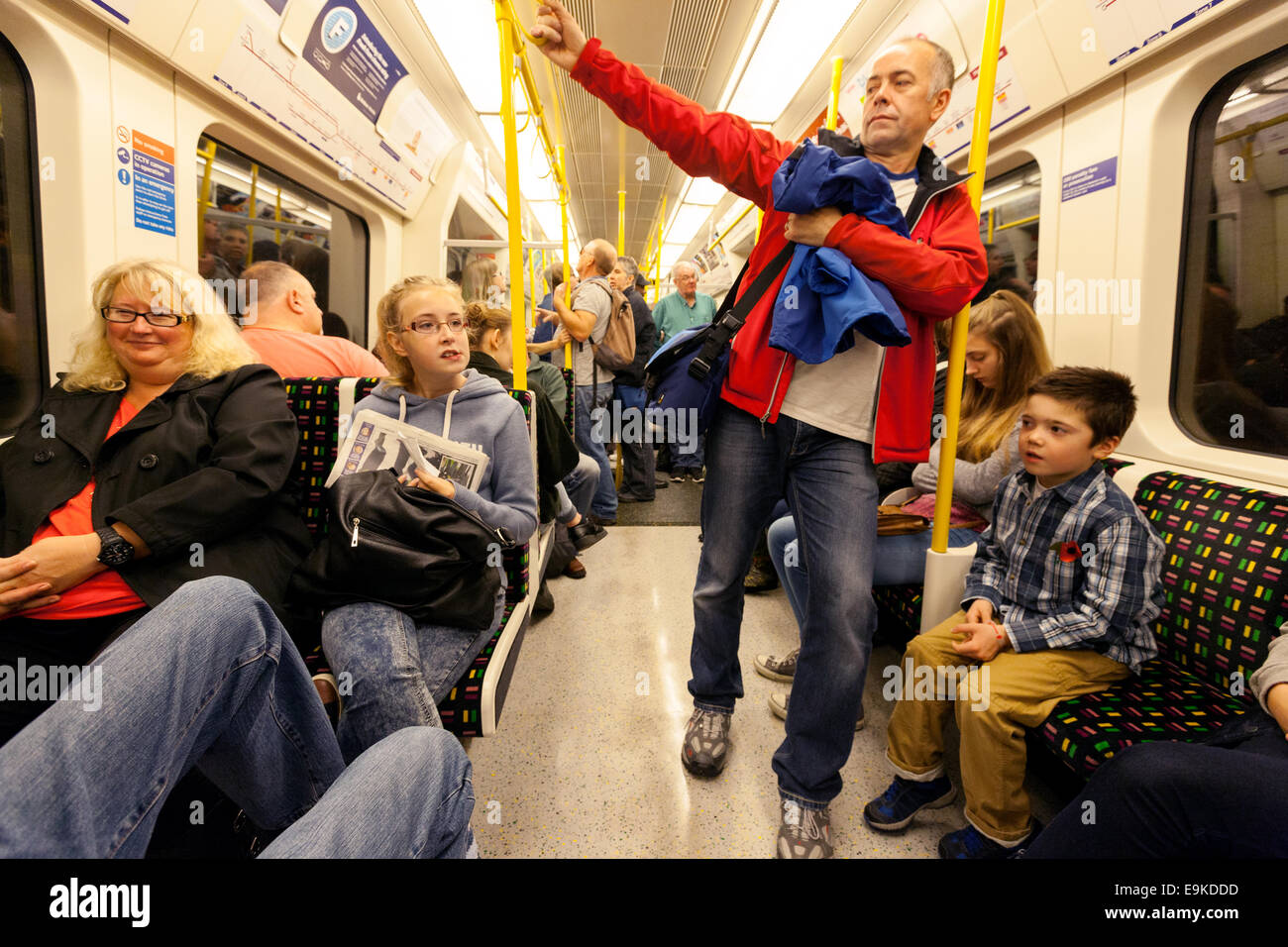 Families with children travelling in a carriage on the London Underground, London UK - Stock Image