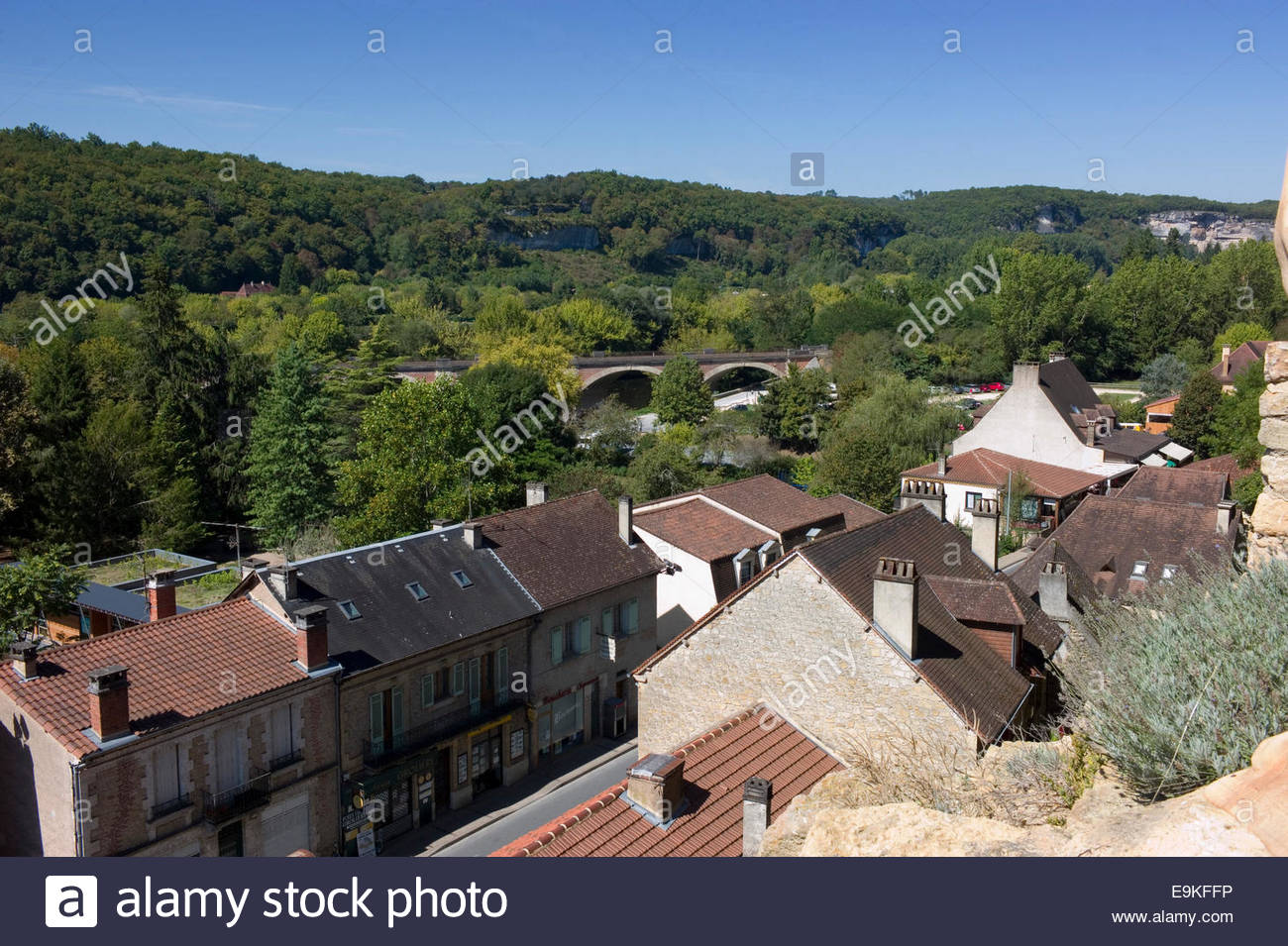 Tiled roofs in the town of Les Eyzies de Tayac En Perigord, Dordogne, France, with the railway viaduct in the distance - Stock Image