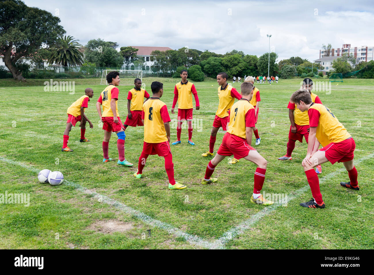Youth football team stretching as part of their warm-up exercise, Cape Town, South Africa - Stock Image