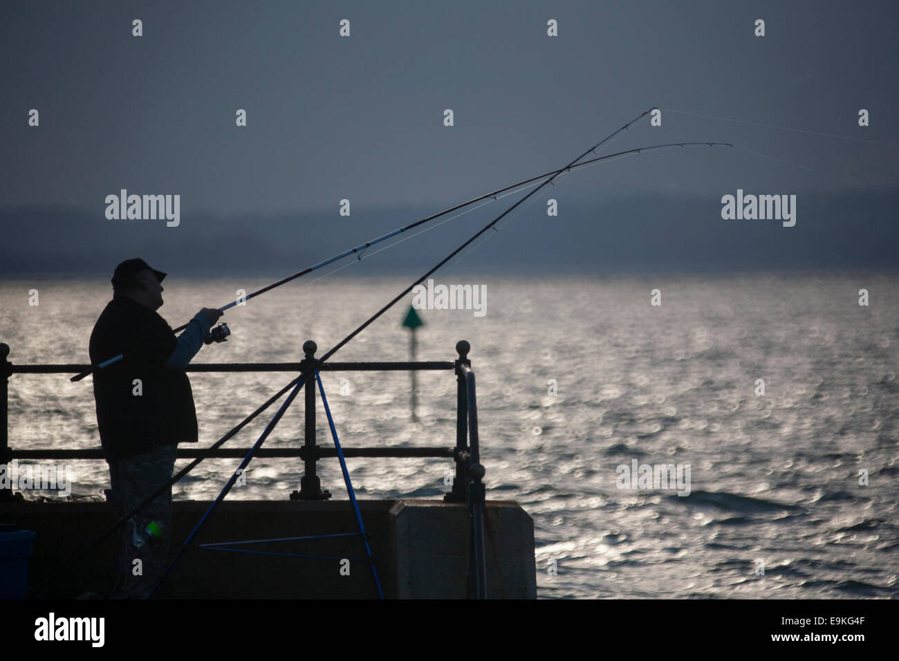 Man, fishing, seafront, silhouette, rods, reel, mirror lens, sea, sparkle, backlit, Cowes, Gurnard, Isle of Wight, - Stock Image