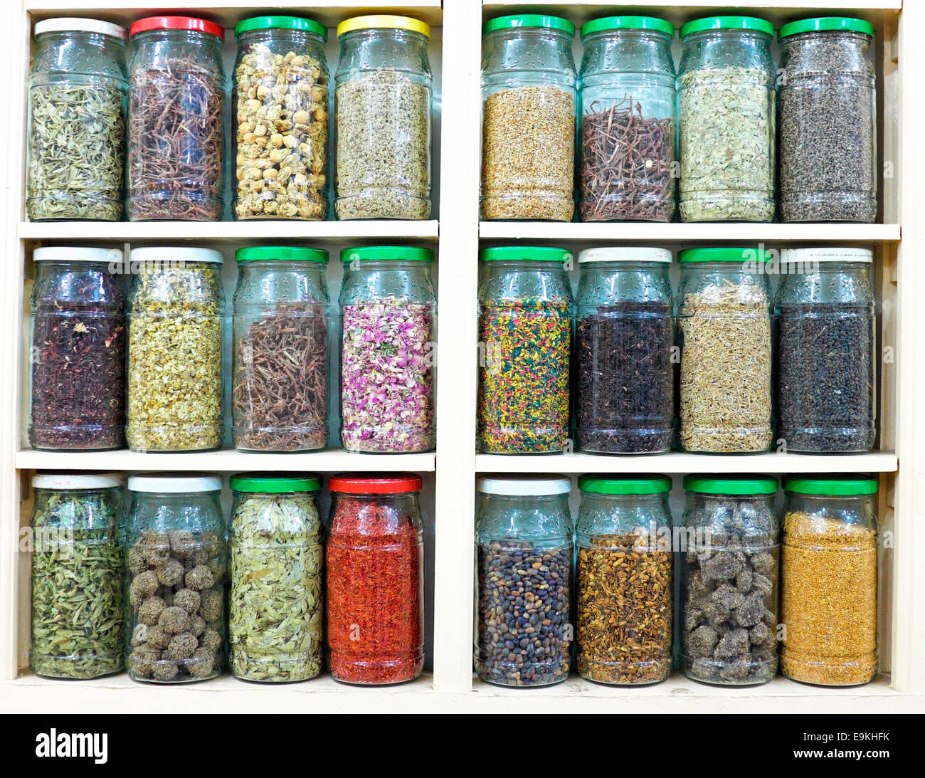assortment of glass jars on shelves in herbalist shop in marrakesh, morocco, containing herbs and spices for medicinal Stock Photo