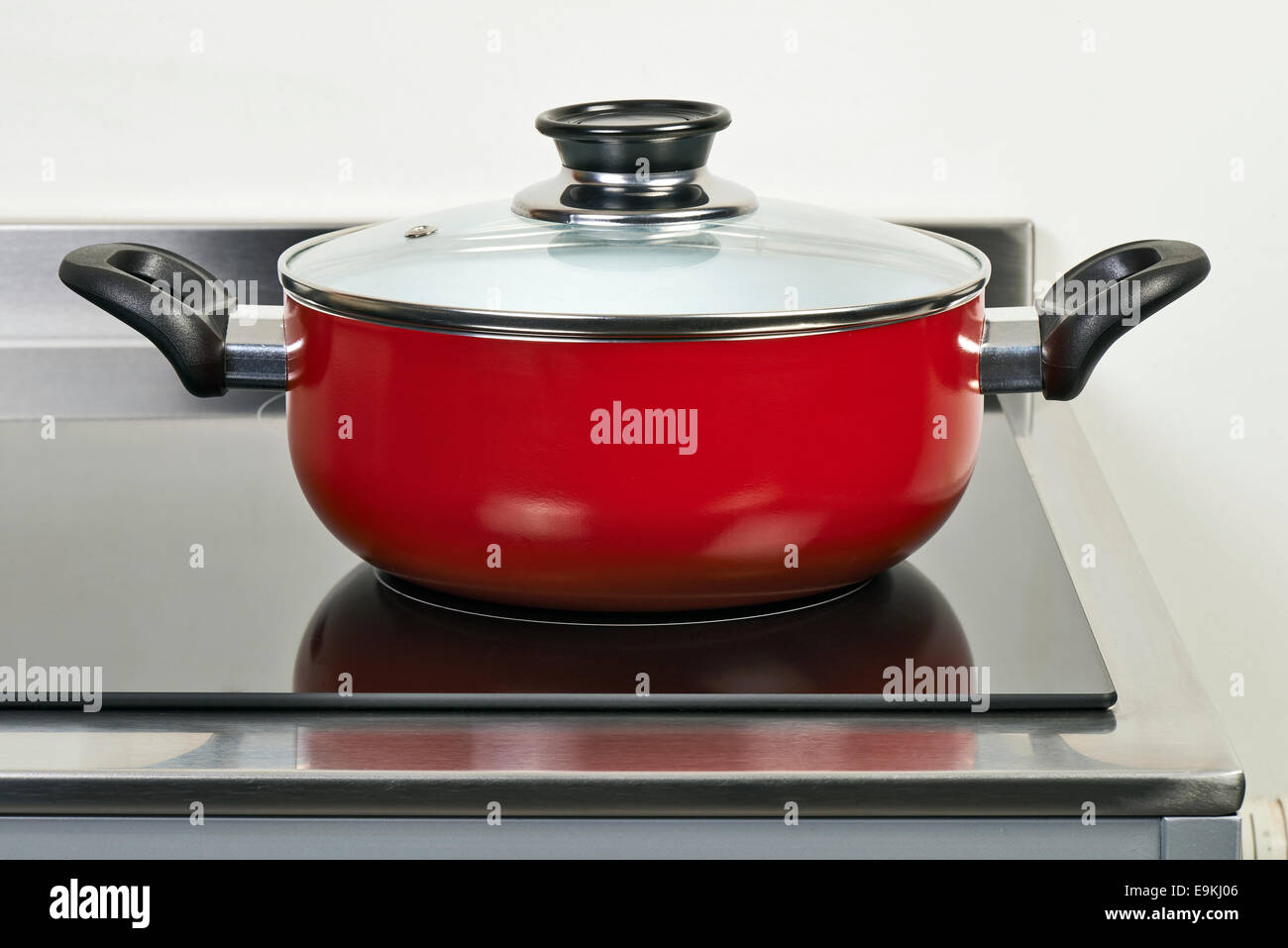Red ceramic pan with cover on Electric hob in modern and domestic kitchen - Stock Image