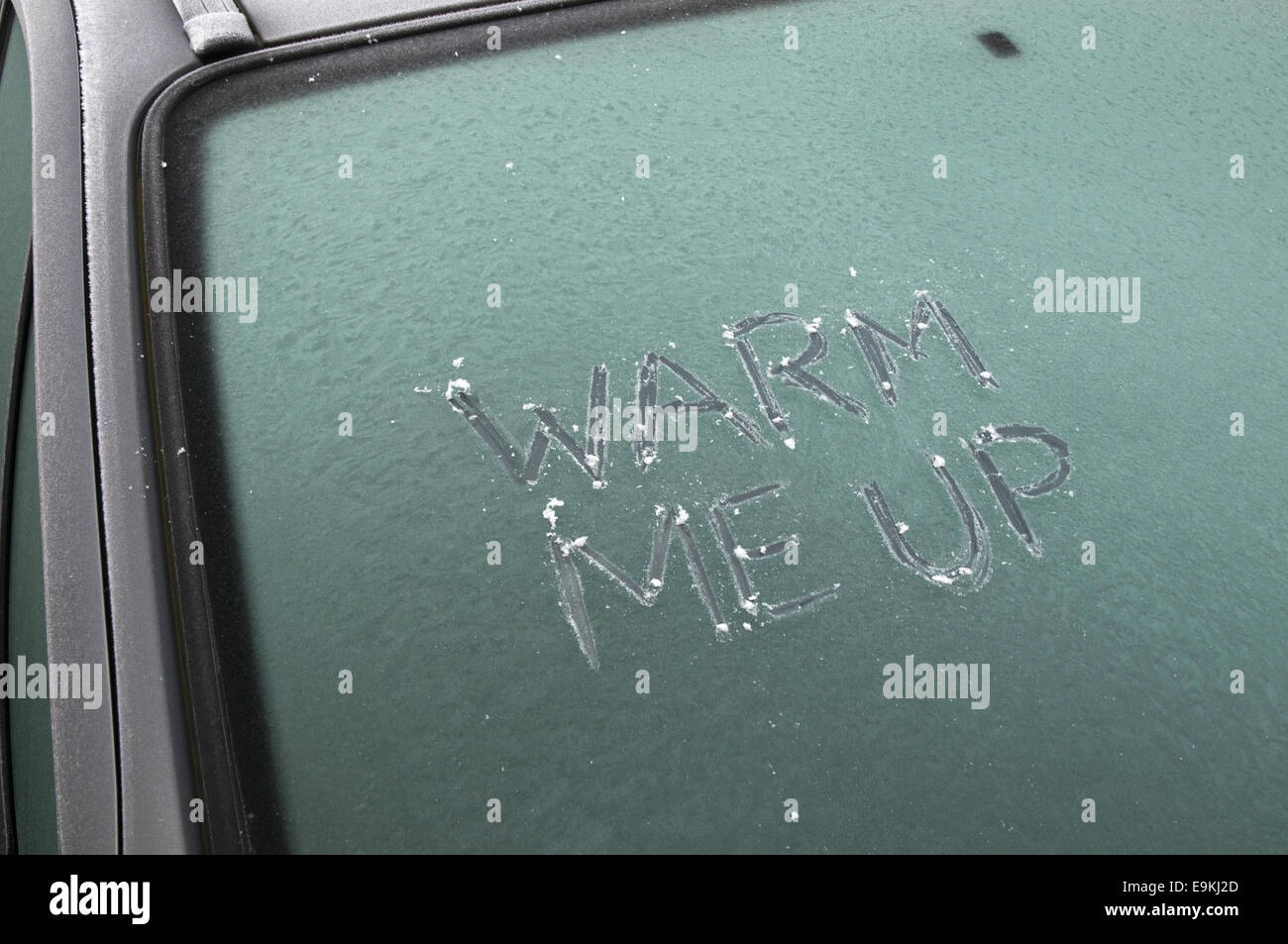 'Warm me up' scratched on to a frosty car windscreen. - Stock Image