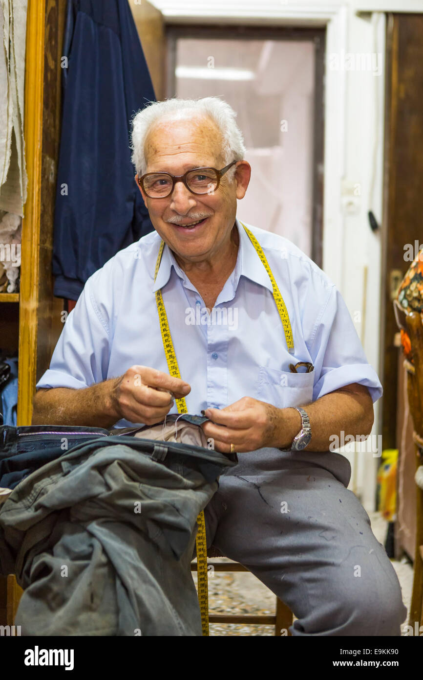 friendly proud senior tailor at work at his shop at the city Zakynthos (Zakynthos, Greece) - Stock Image