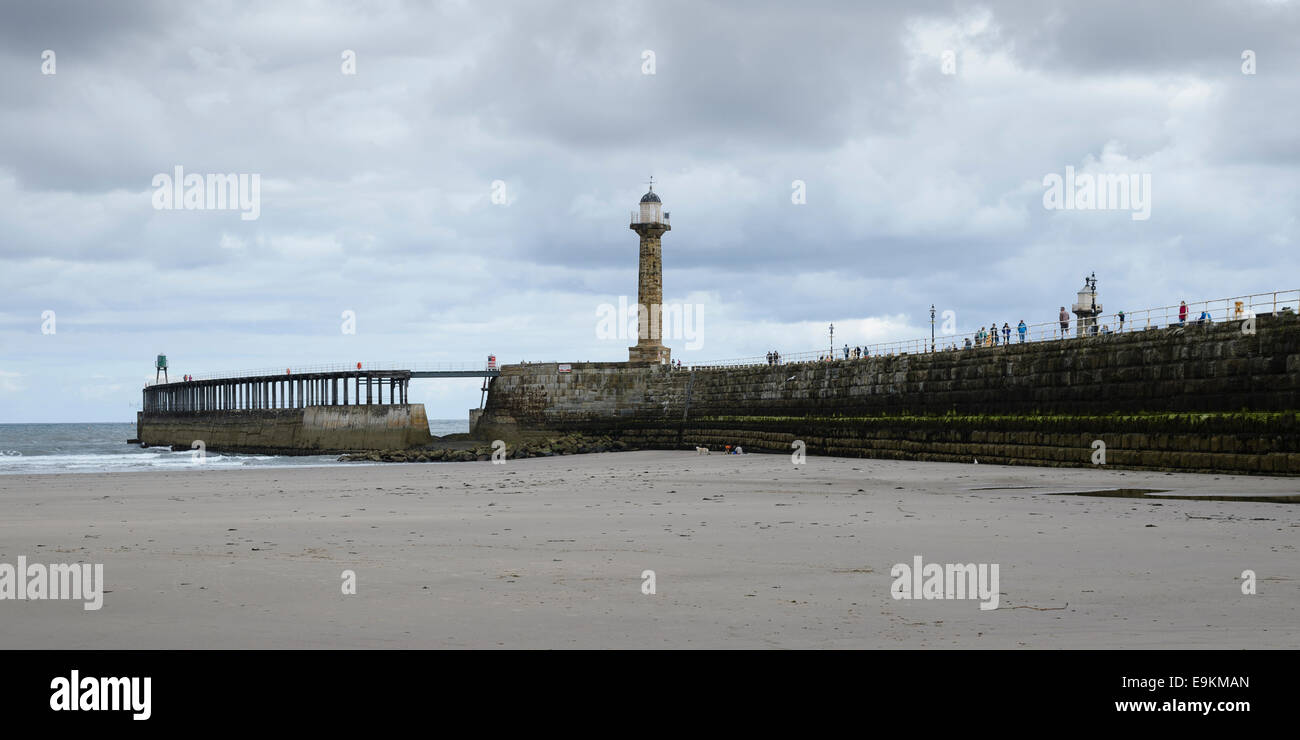 Whitby Pier and lighthouse from the beach on a cloudy, overcast summer's day. - Stock Image