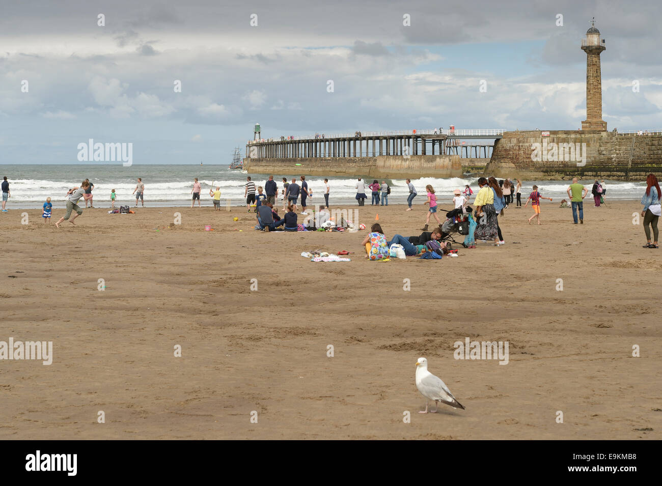 Holidaymakers on the beach on an overcast a cloudy summer day near Whitby Pier, N Yorks, UK. - Stock Image