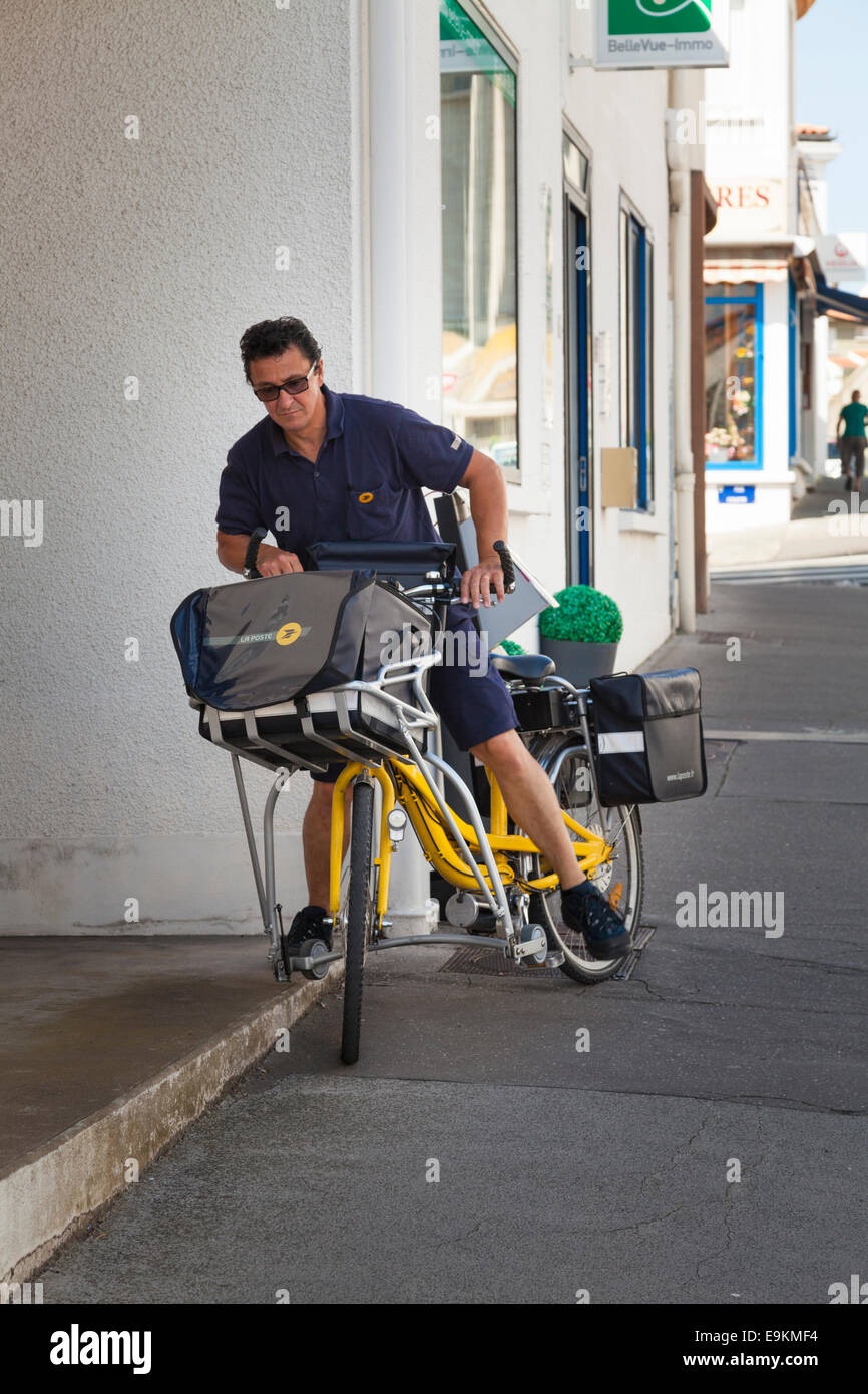 La Poste French postman on bicycle with outrigger stabilisers - Stock Image