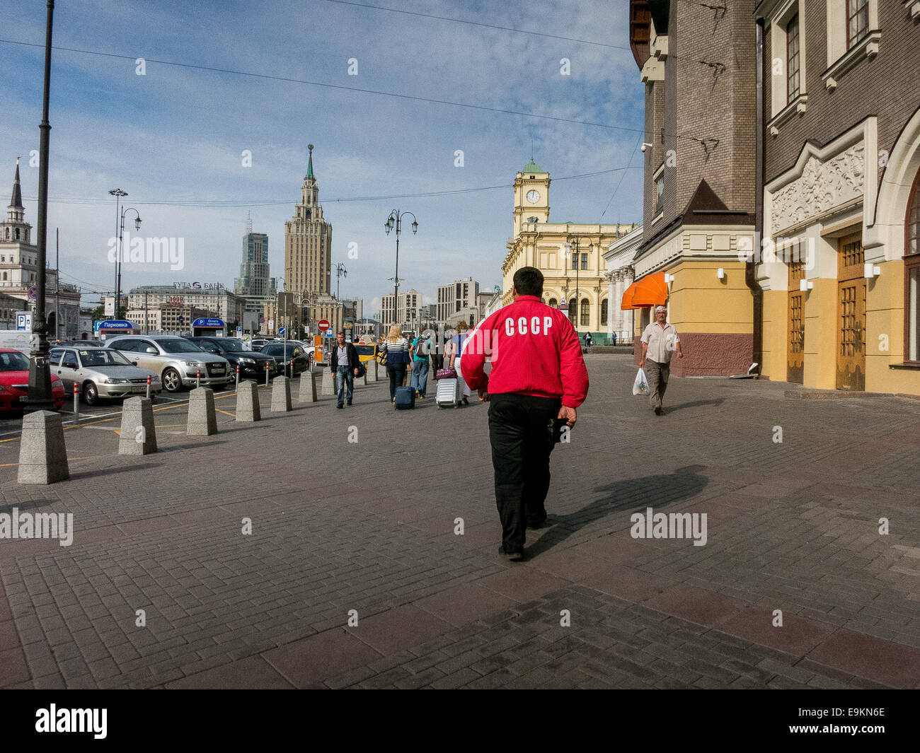 A man wearing a red jacket with Soviet emblem CCCP walking on the street in Moscow. - Stock Image