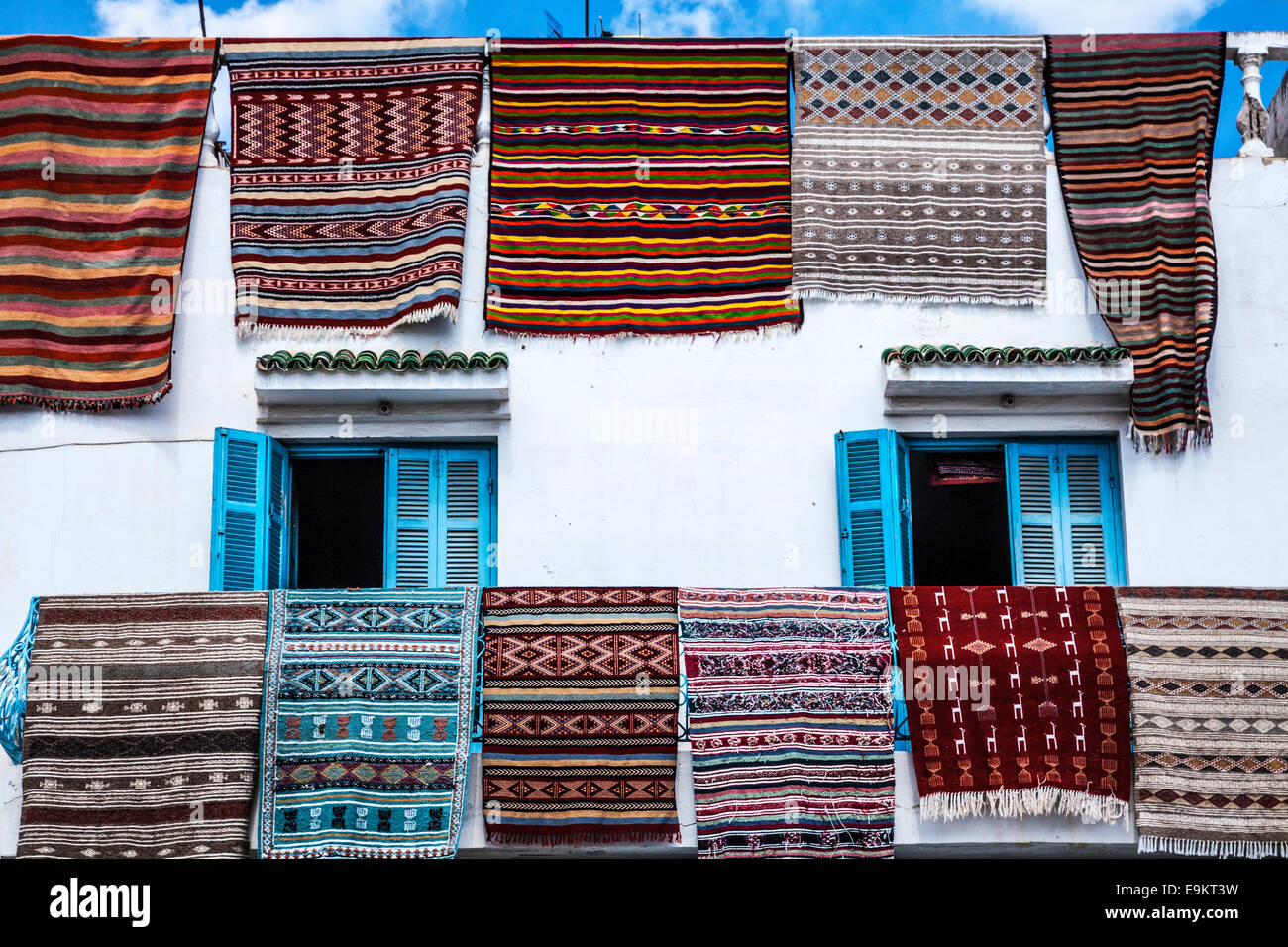 Carpets and rugs hanging out on display from a shop in the Place de la Grande Mosque in Sousse,Tunisia. - Stock Image