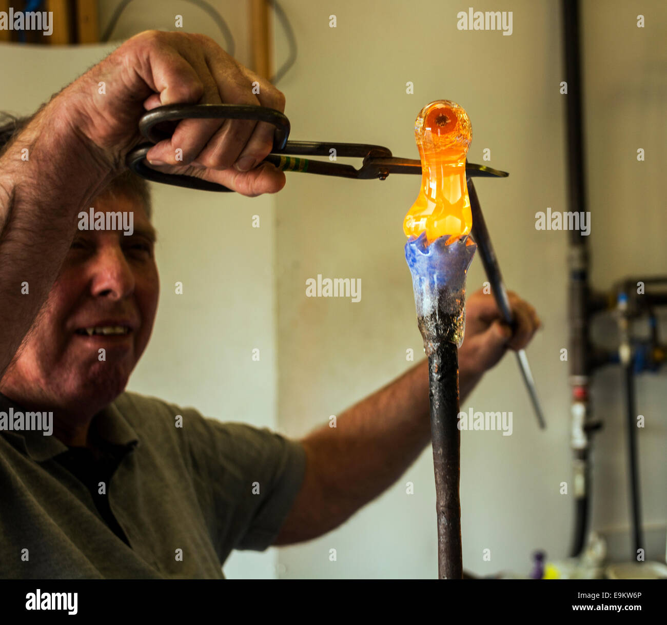 A highly skilled craftsman adds molten glass to a paperweight in production, judging the exact amount from years Stock Photo