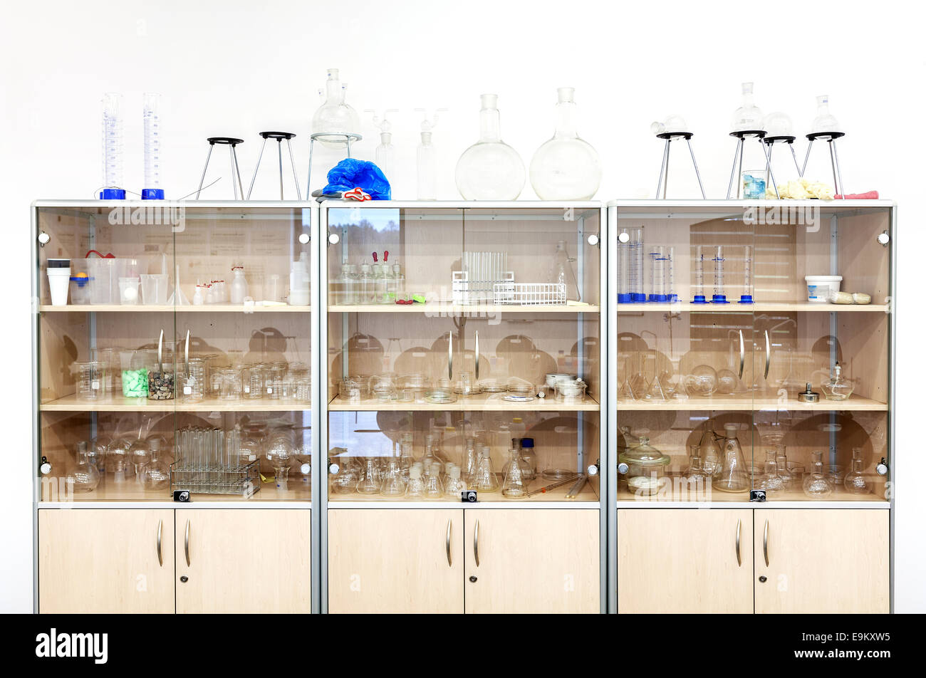 Different laboratory glassware and equipment on shelves. - Stock Image