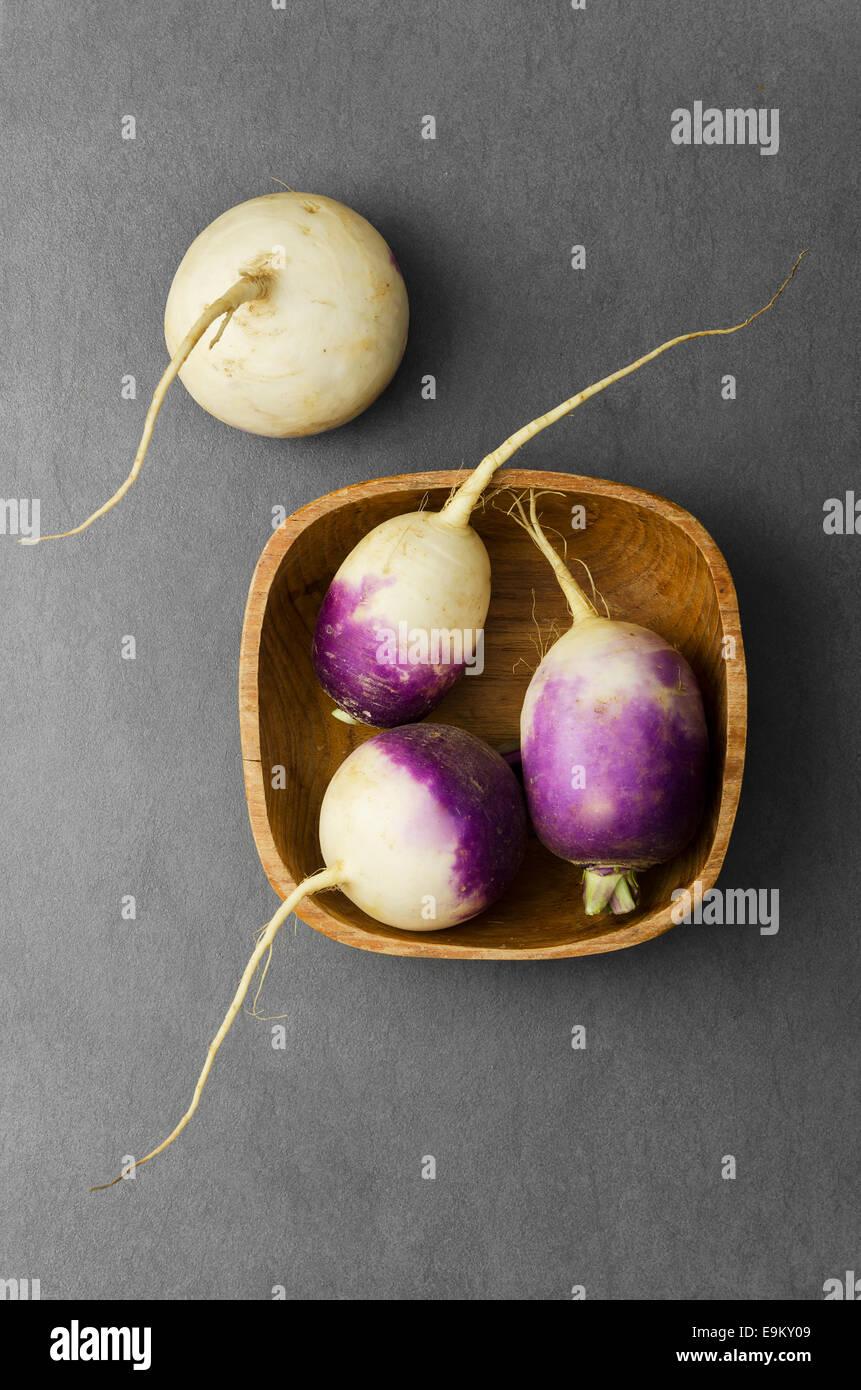 Organic turnips in bowl over dark background - Stock Image