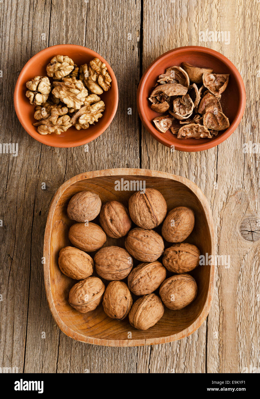 Walnuts, core and nutshell in rustic bowls over wooden table - Stock Image