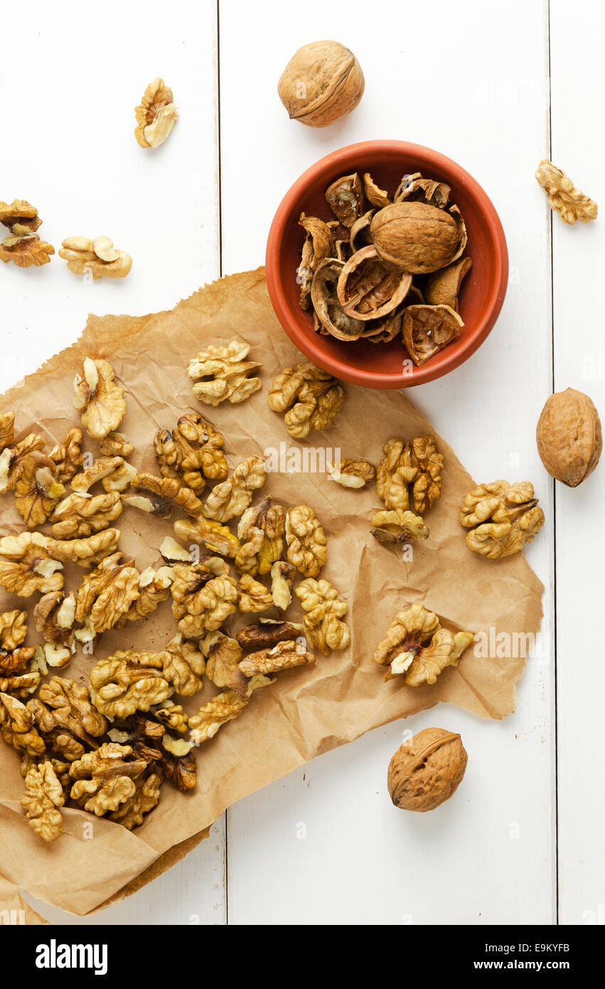 Walnuts core, nutshell and walnuts over white table - Stock Image