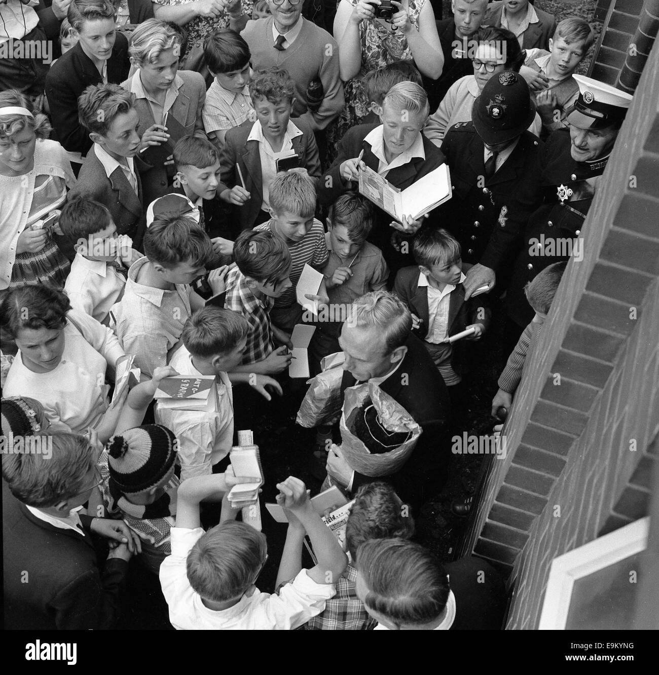 Football fans autograph hunters children crowd around Billy Wright after his final match at Molineux August 8th - Stock Image