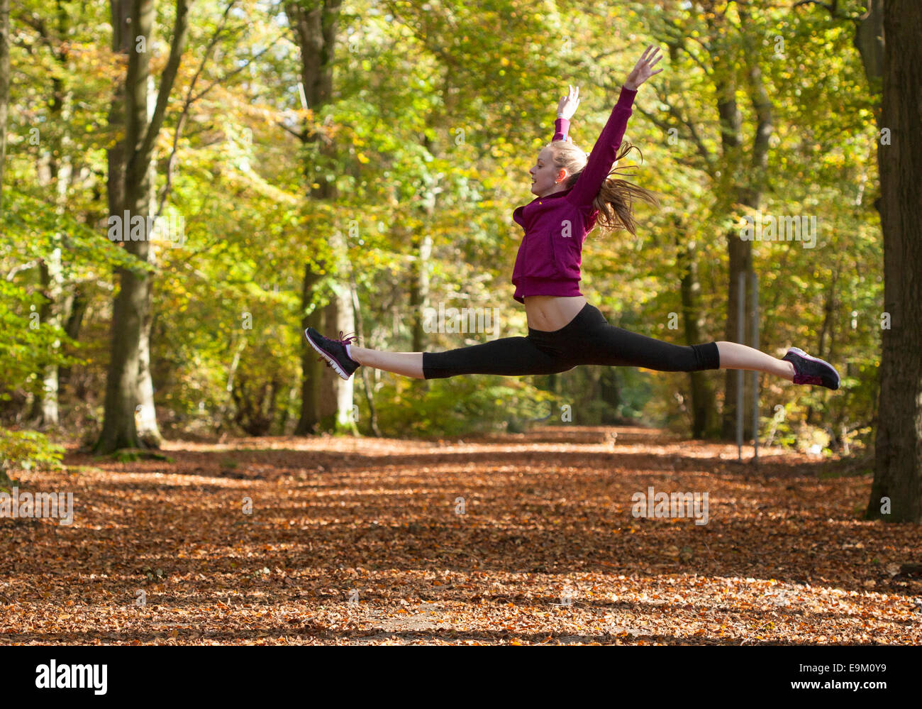 young woman doing split leap jump in autumn woods - Stock Image