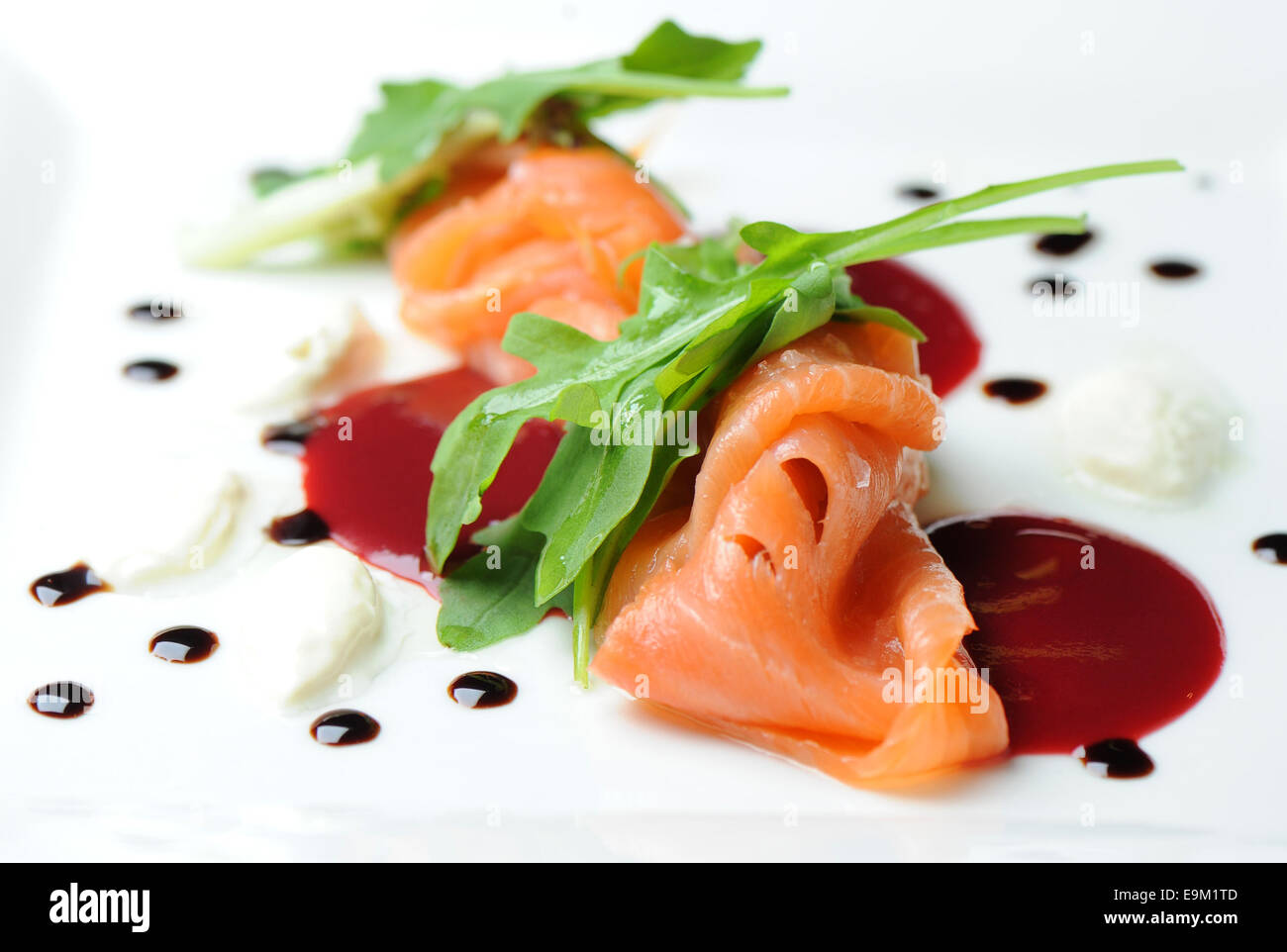 Smoked salmon gravlax served as a starter on a white plate with chilli sauce. - Stock Image