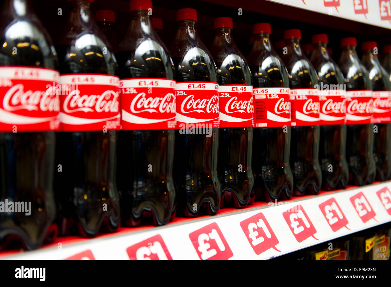Coca Cola on sale on a supermarket shelf. Doctors have warned fizzy drinks can lead to tooth decay and diabetes - Stock Image