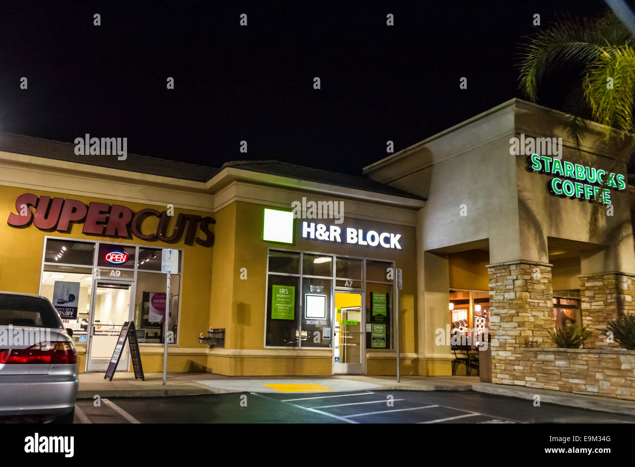 A strip mall in Modesto California with a Supercuts, H&R Block tax preparers, and a Starbucks coffee at night - Stock Image