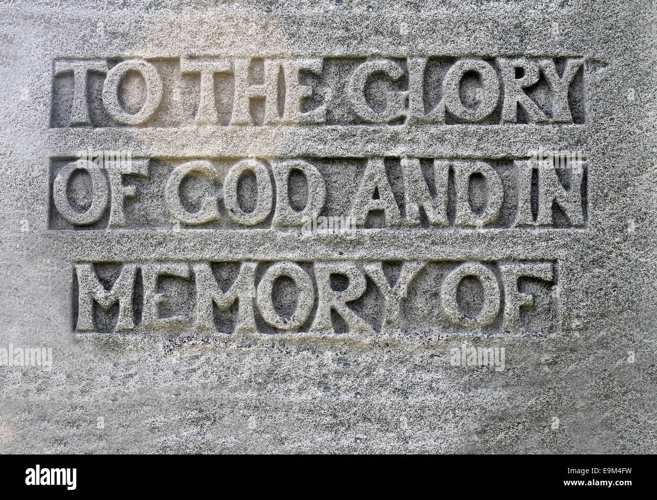 Closeup of a religious eulogy on a gravestone saying to the glory of God and in the memory of with copy space. - Stock Image