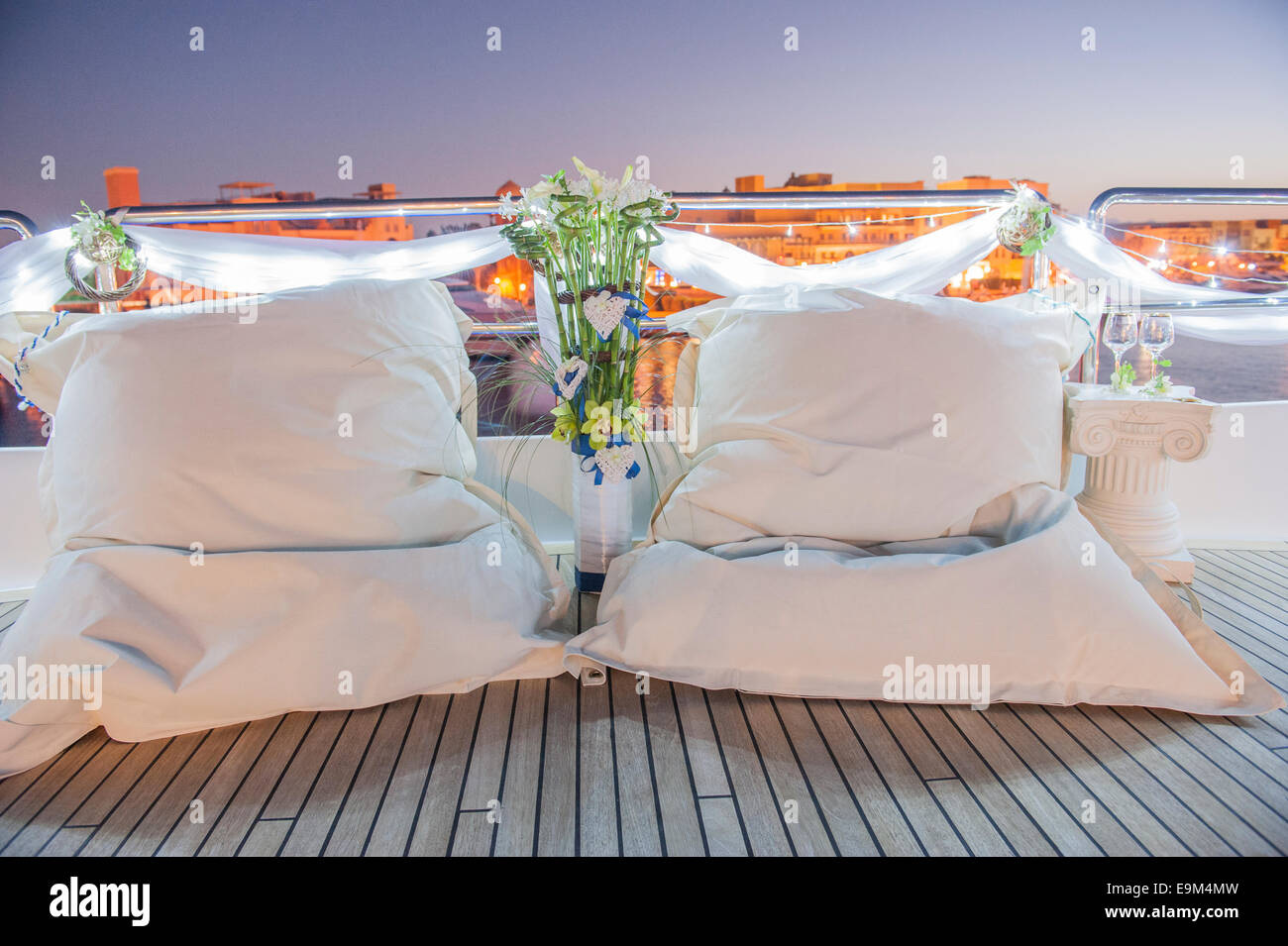 Pair of large white bean bag cushions on deck of boat in marina - Stock Image