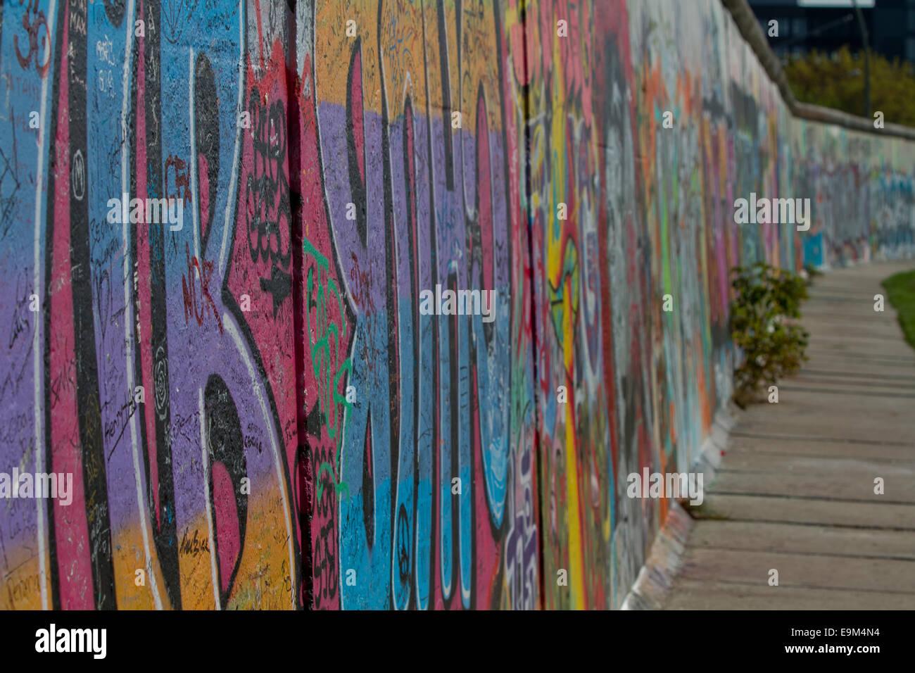 Graffiti street art Berlin wall pavement - Stock Image