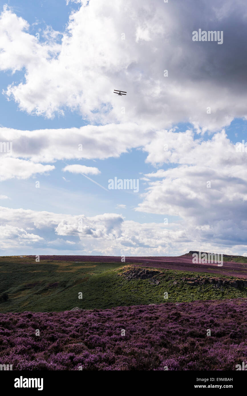 Bi plane flying over the Peak District Derbyshire rugged moorland covered in purple heather during August England - Stock Image