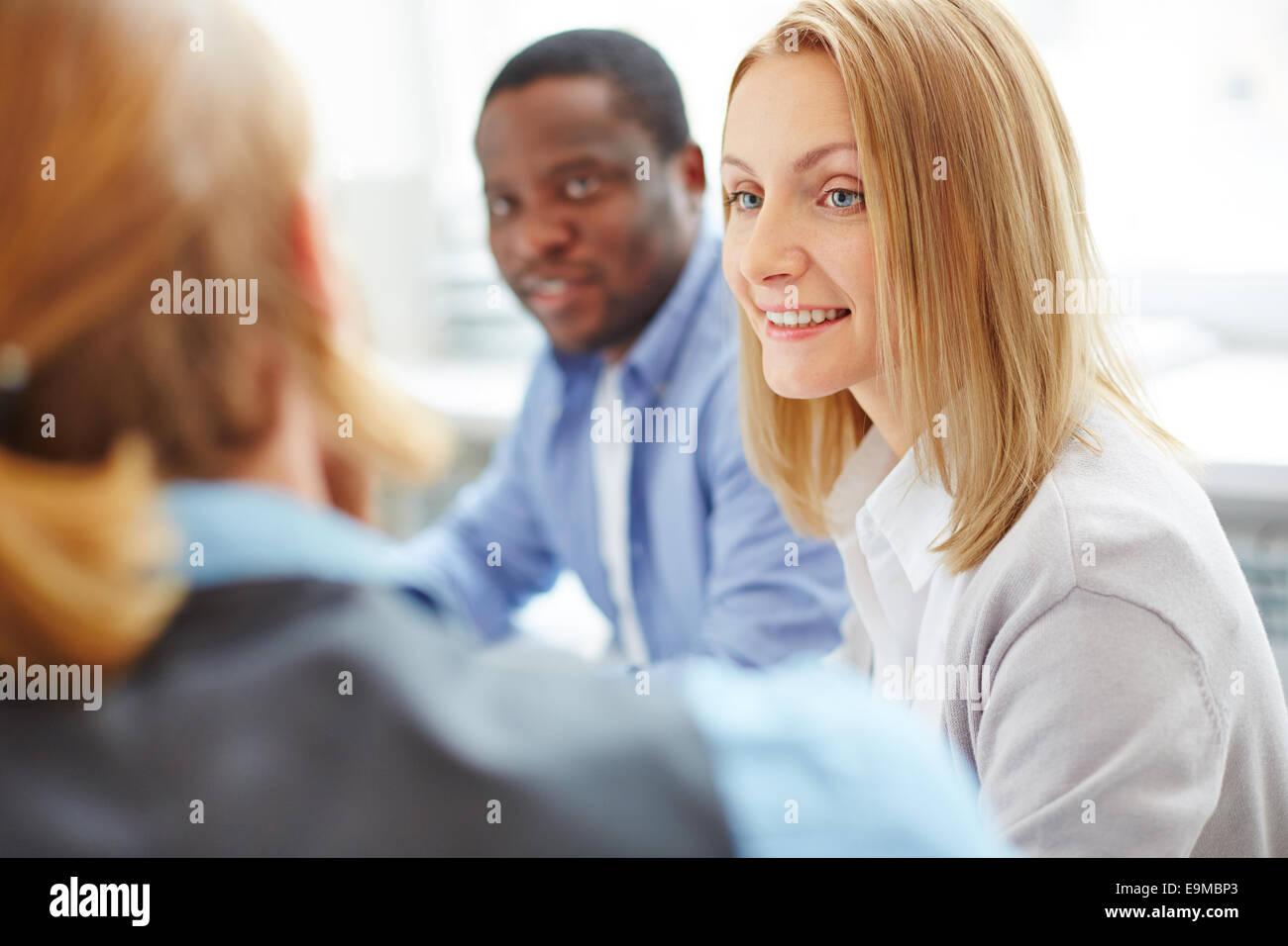 Smiling businesswoman between her co-workers - Stock Image