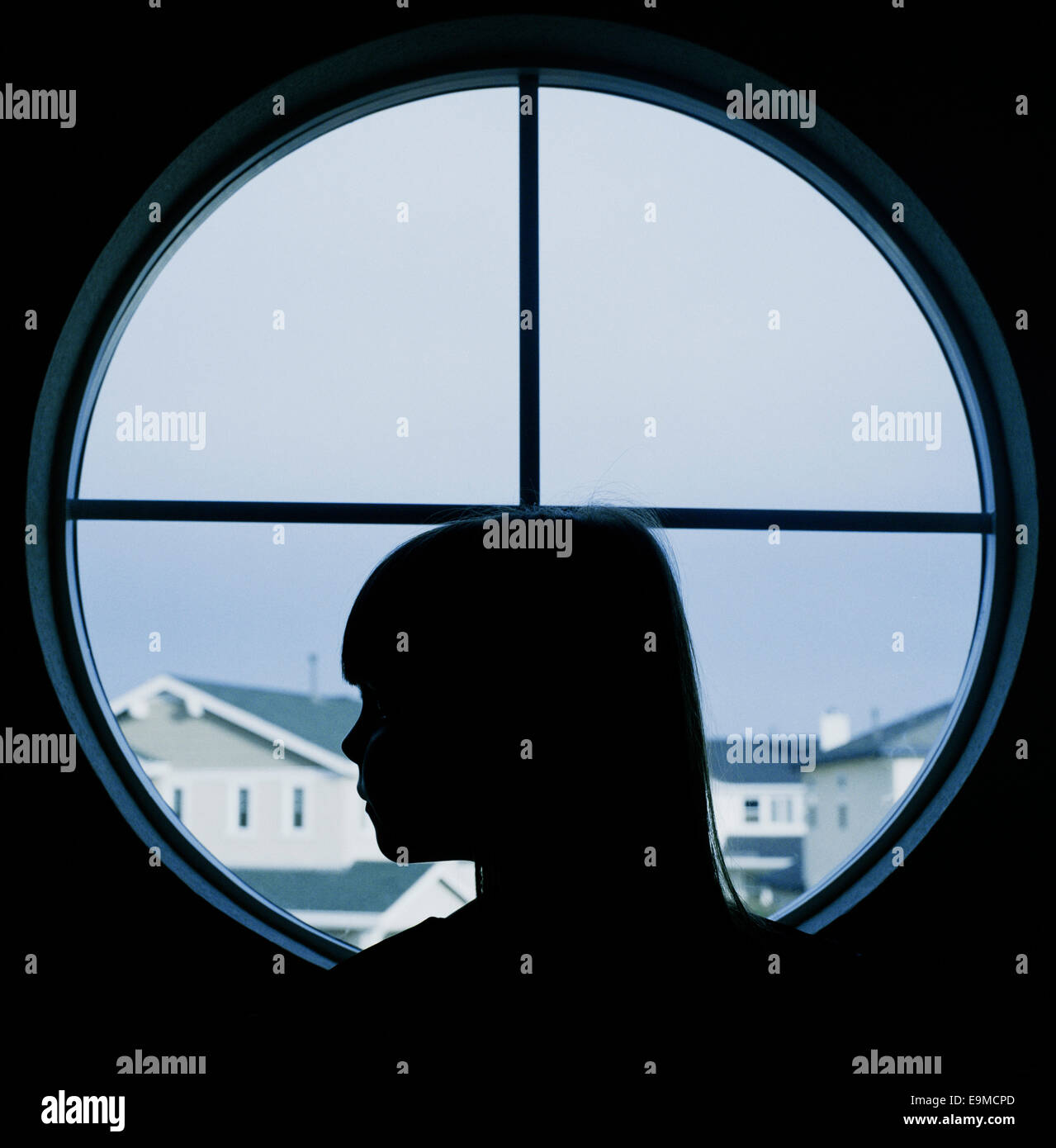 A child in profile in a round window - Stock Image