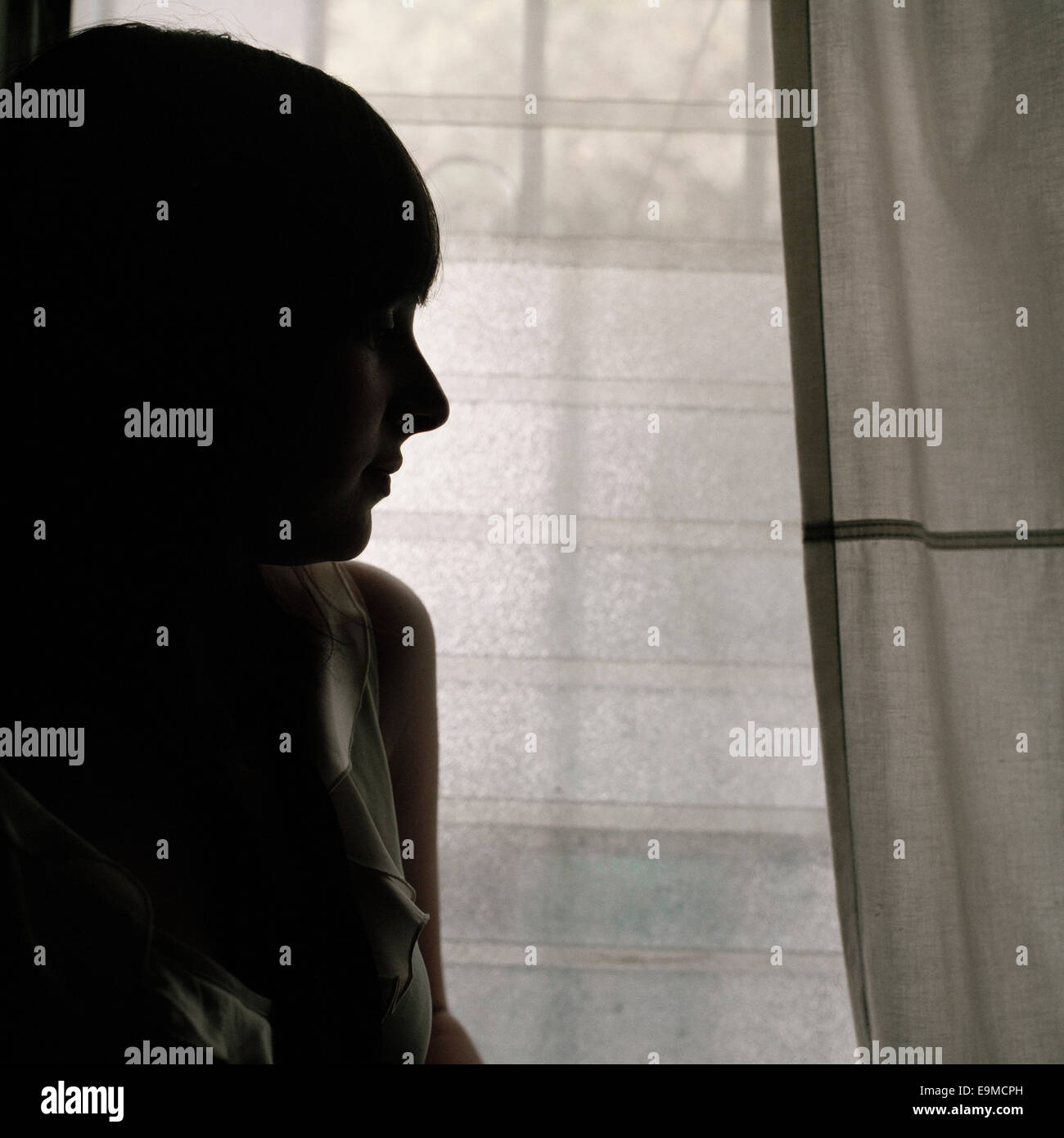 A woman standing next to a window Stock Photo
