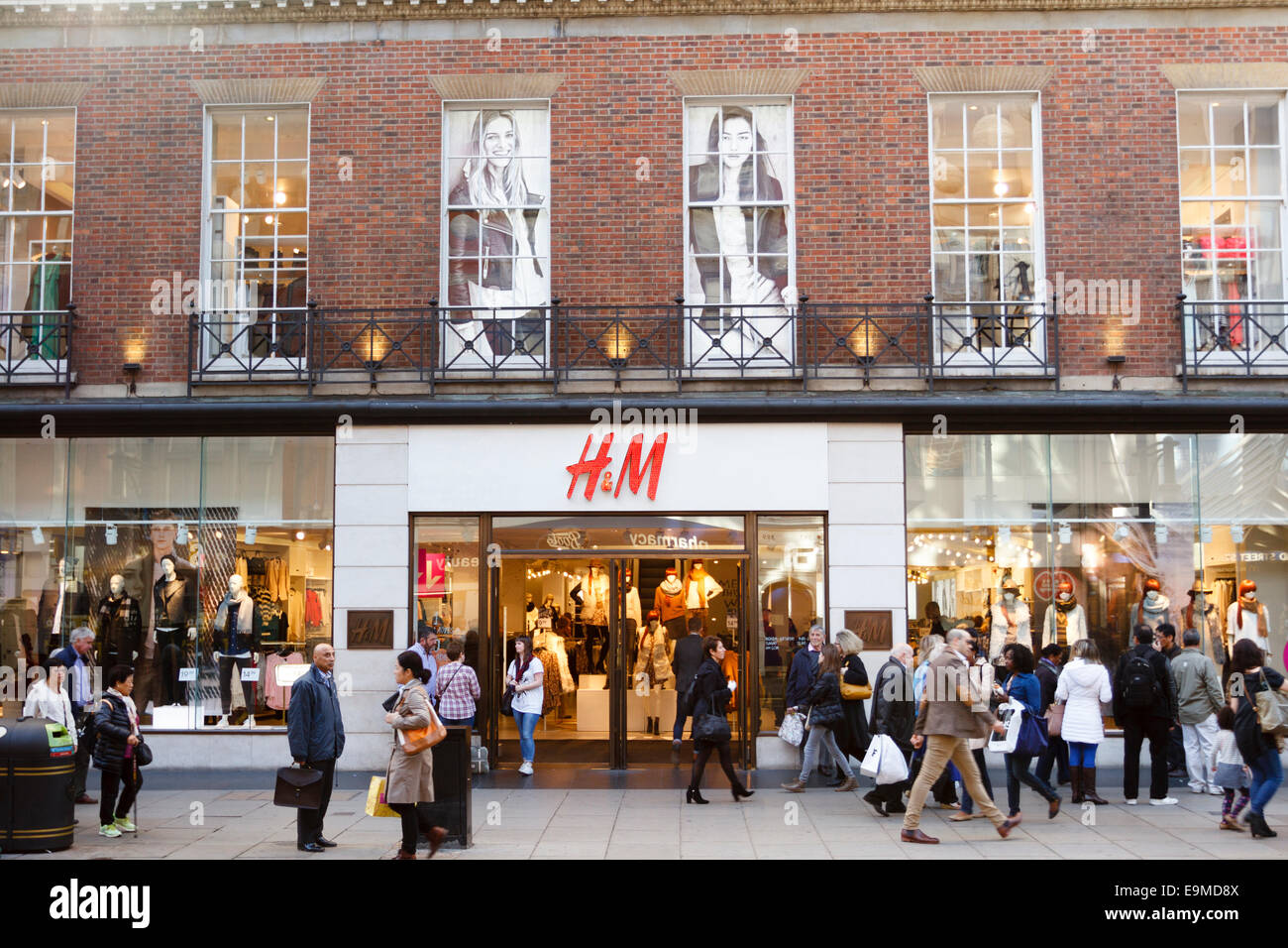 Crowds of shoppers walk past  the H&M shop/store Oxford Street, London, England, UK - Stock Image
